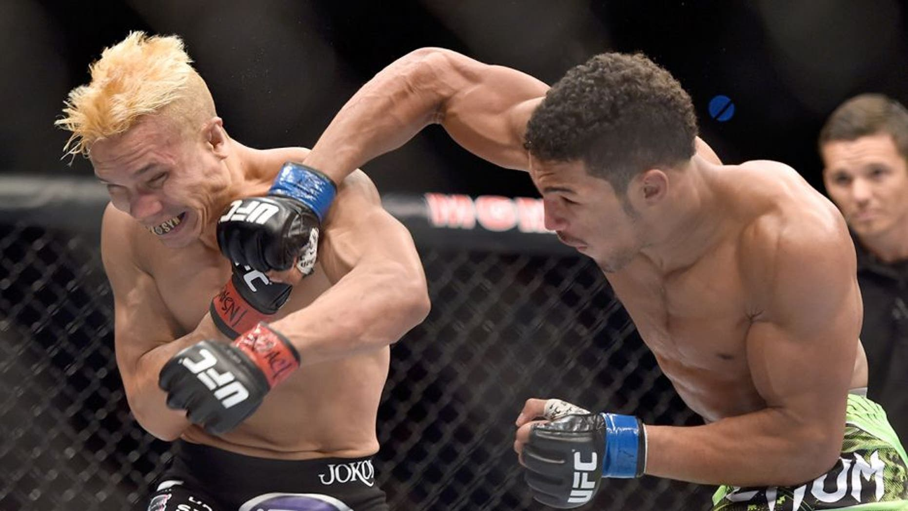 LAS VEGAS, NV - SEPTEMBER 27: Kevin Lee punches Jon Tuck in their lightweight fight during the UFC 178 event inside the MGM Grand Garden Arena on September 27, 2014 in Las Vegas, Nevada. (Photo by Jeff Bottari/Zuffa LLC/Zuffa LLC via Getty Images)