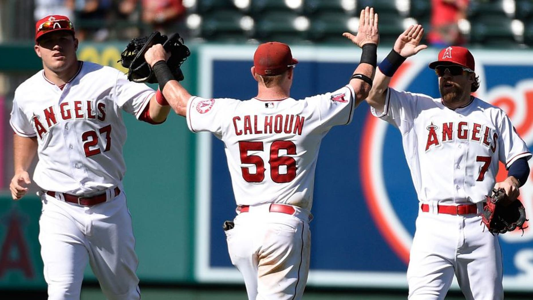 Sep 27, 2015; Anaheim, CA, USA; Los Angeles Angels center fielder Mike Trout (27) and right fielder Kole Calhoun (56) and left fielder Collin Cowgill (right) celebrate after the game against the Seattle Mariners during the ninth inning at Angel Stadium of Anaheim. The Angels won 3-2. Mandatory Credit: Kelvin Kuo-USA TODAY Sports