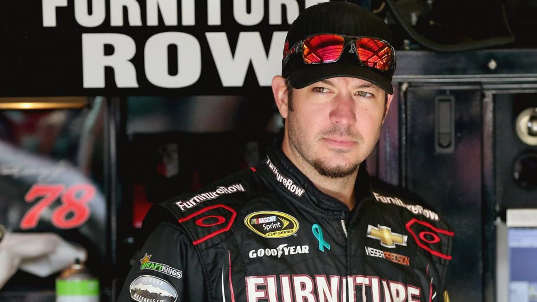 Martin Truex Jr, driver of the #78 Furniture Row/Visser Precision Chevrolet, stands in the garage area during practice for the NASCAR Sprint Cup Series MyAFibRisk.com 400 at Chicagoland Speedway on September 19, 2015 in Joliet, Illinois. (Photo by Jonathan Daniel/Getty Images)