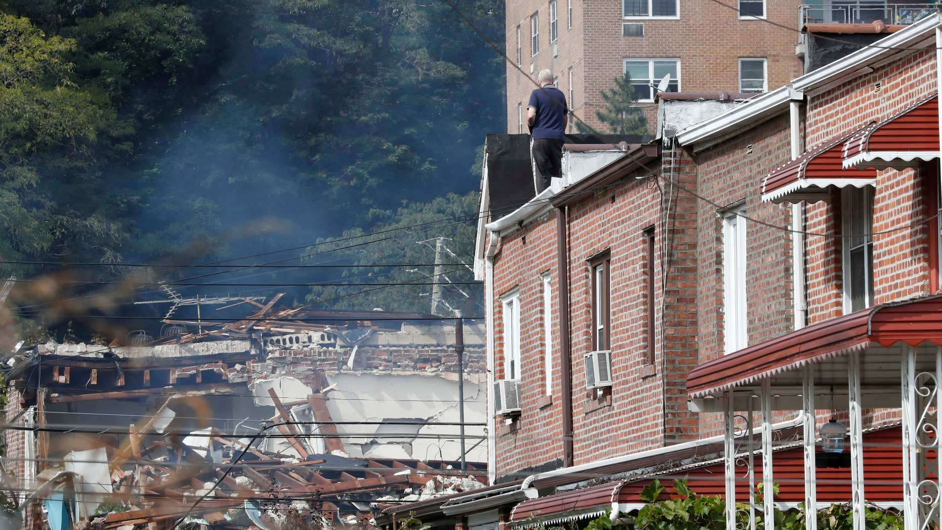 A man watches emergency service personnel work at the scene of a house explosion from a roof, Tuesday, Sept. 27, 2016, in the Bronx borough of New York.