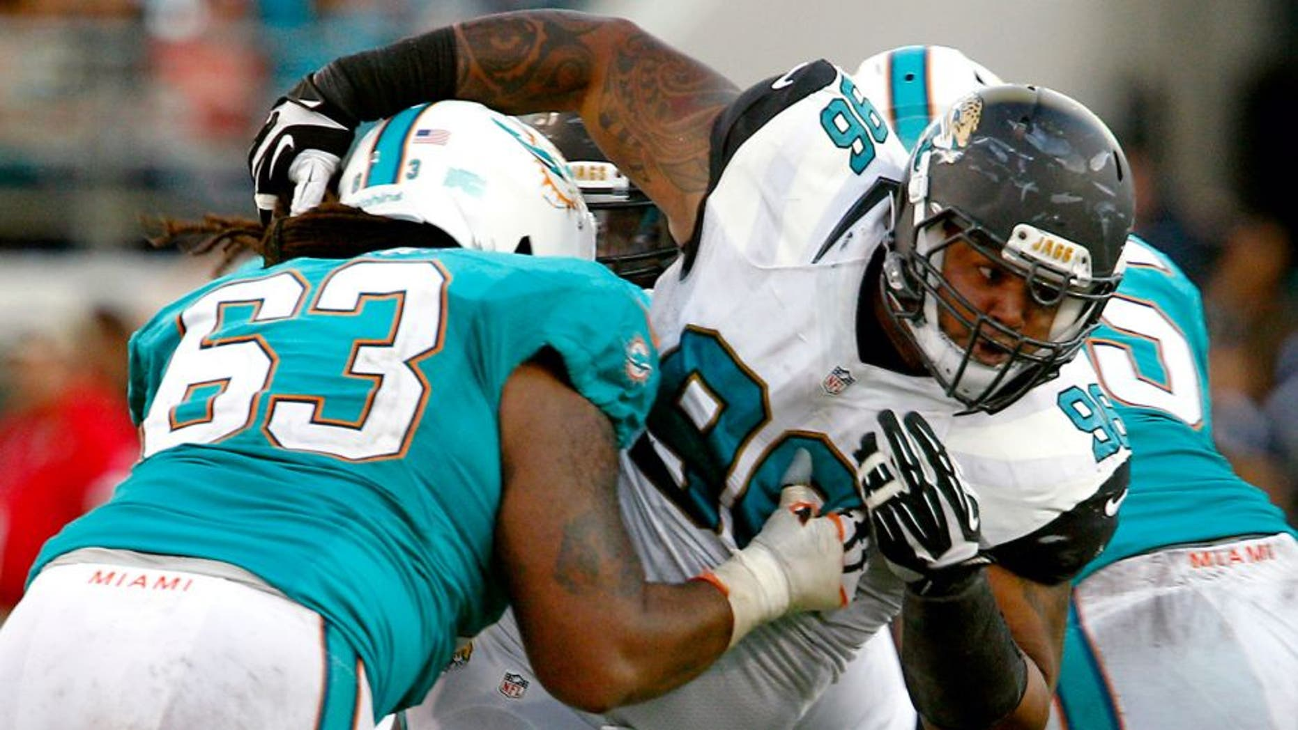 Sep 20, 2015; Jacksonville, FL, USA; Jacksonville Jaguars defensive tackle Michael Bennett (96) is held by Miami Dolphins offensive guard Dallas Thomas (63) during the second half of an NFL Football game at EverBank Field. The Jacksonville Jaguars won 23-20. Mandatory Credit: Reinhold Matay-USA TODAY Sports