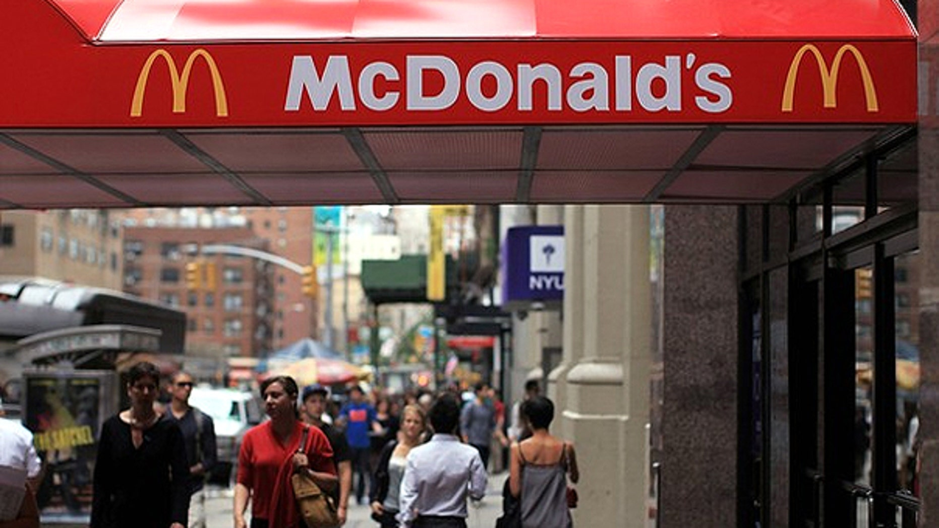Sept. 9: People walk by a McDonalds in New York City. McDonald's Corp. is one of the 222 companies that have notified federal regulators it's health insurance plan for nearly 30,000 hourly restaurant workers isn't compatible with a new requirement of the U.S. health overhaul.