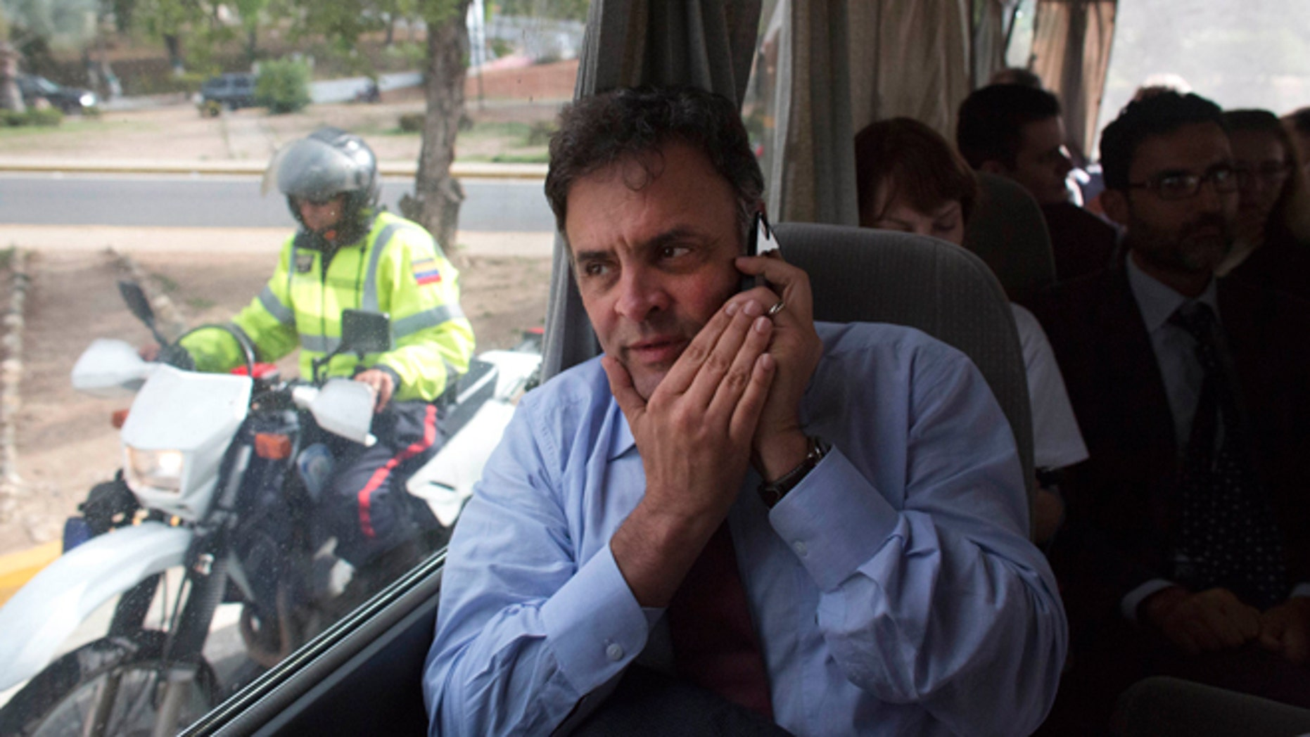 Brazilian Senator Aecio Neves speaks on his cell phone as he rides in a van with other Brazilian senators, escorted by Bolivarian Police on motorcycles, after departing the airport in La Guaira, Venezuela, Thursday, June 18, 2015. The group of Brazilian senators failed to reach the capital city of Caracas twice, due to traffic caused by a demonstration and road maintenance. The delegation had traveled to Venezuela to meet with members of Venezuela's opposition but returned to the airport to fly back to Brazil. (AP Photo/Ariana Cubillos)