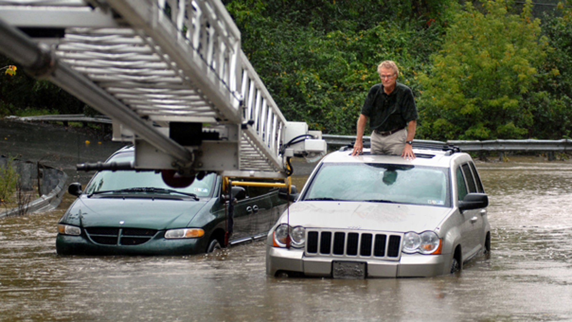 Sept. 30: A stranded motorist waits for the fire company ladder to be lowered to him in Lancaster, Pa. A series of storms moving through Pennsylvania brought flooding that closed some roadways and prompted many schools to dismiss classes early.