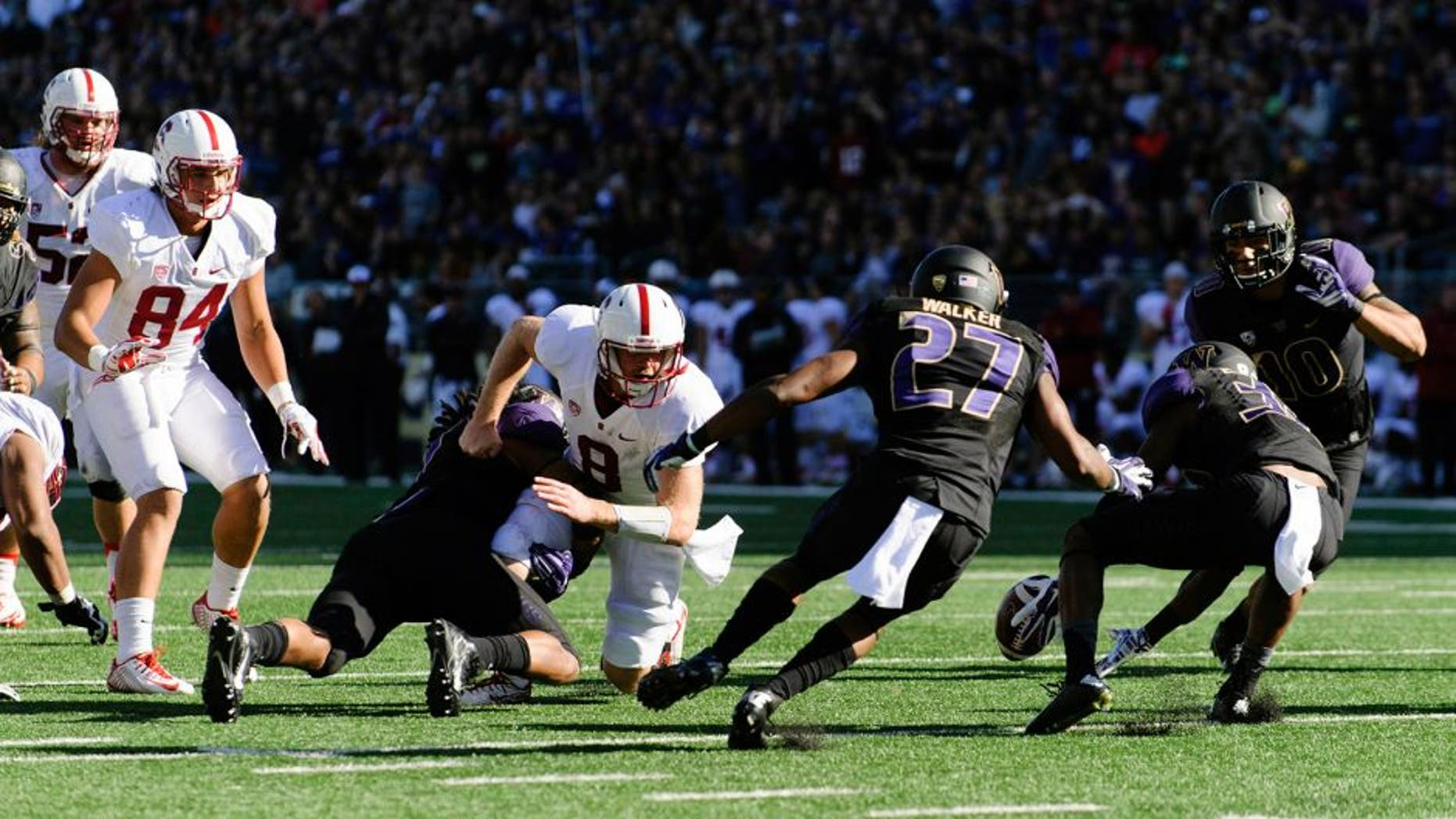 Sep 27, 2014; Seattle, WA, USA; Washington Huskies defensive back Budda Baker (32) reaches for the fumbled ball by Stanford Cardinal safety Jordan Richards (8) during the second half at Husky Stadium. Stanford defeated Washington 20-13. Mandatory Credit: Steven Bisig-USA TODAY Sports