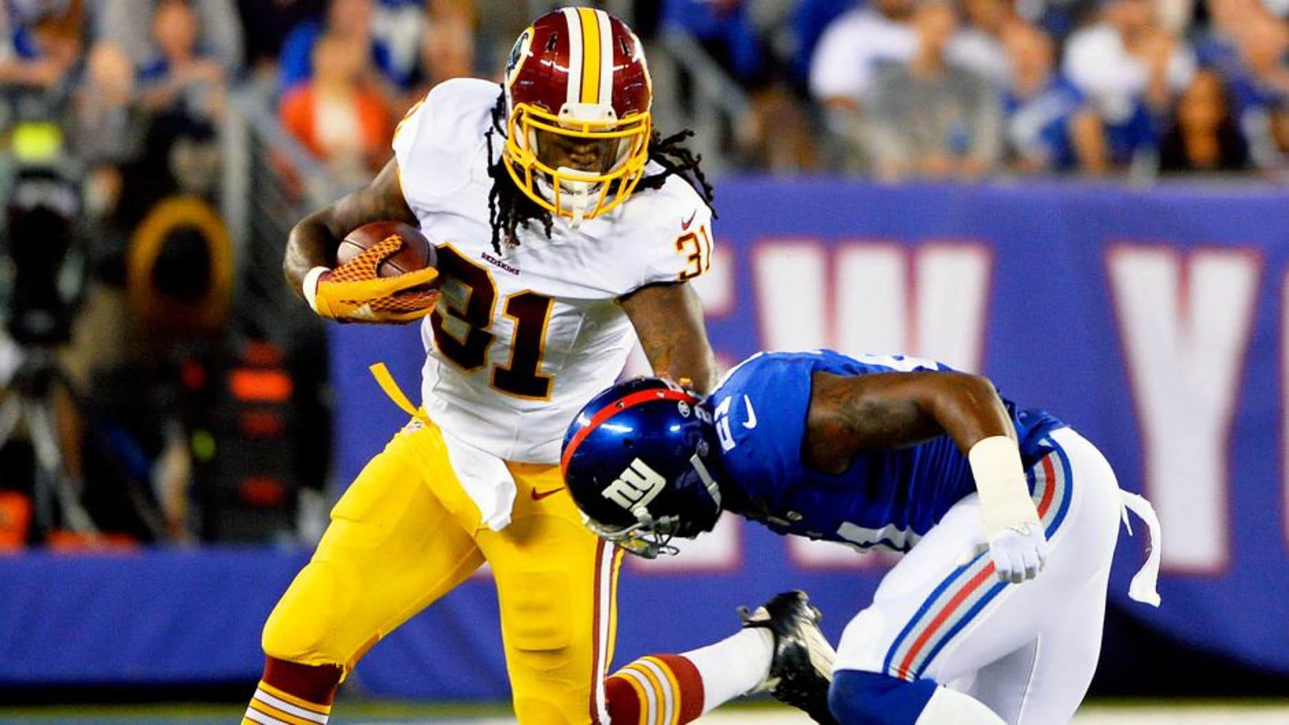 EAST RUTHERFORD, NJ - SEPTEMBER 24: Matt Jones #31 of the Washington Redskins tries to avoid the tackle of Landon Collins #21 of the New York Giants in the second quarter at MetLife Stadium on September 24, 2015 in East Rutherford, New Jersey. (Photo by Alex Goodlett/Getty Images)