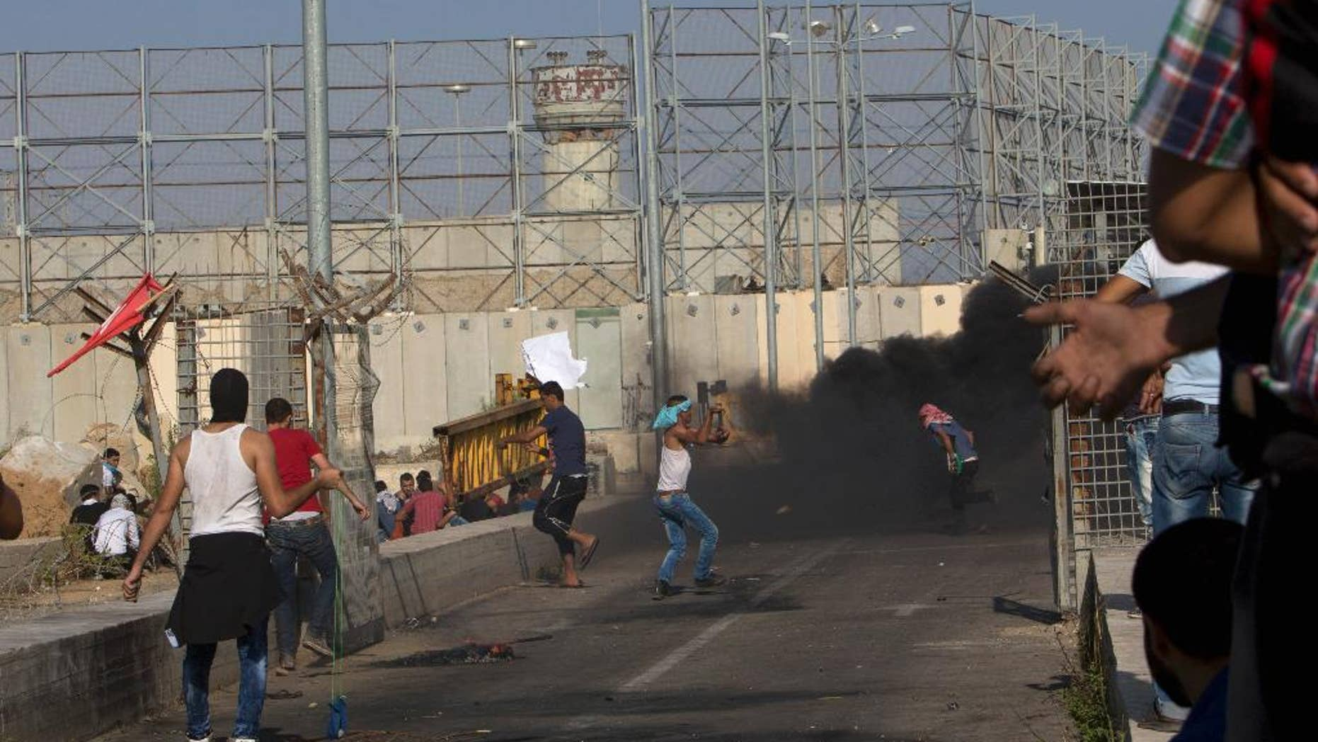 FILE - In this Oct. 16, 2015 file photo, Palestinian demonstrators hurl stones at Israeli soldiers during clashes at the entrance of Erez border crossing between the Gaza Strip and Israel, in the northern Gaza Strip. An Israeli advocacy group is reporting a sharp jump in the number of Palestinians from the Gaza Strip who have been summoned for questioning by Israeli security agents as a condition for leaving the blockaded territory. Gisha, which pushes for freedom of movement for Gaza's 1.8 million people, says more than 1,200 Gazans underwent interrogations during the first half of this year. (AP Photo/Adel Hana, File)