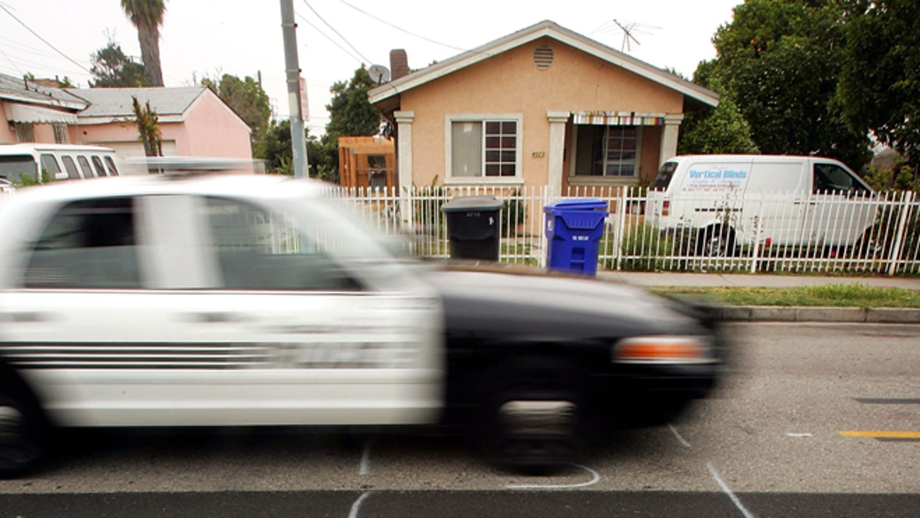 """MAYWOOD, CA - MAY 17:  A police car drives down a residential street marked to be dug up for service with shorthand letters for """"underground service alert"""" on May 17, 2006 in the Los Angeles-area city of Maywood, California. According to reports, the Maywood City Council has declared the municipality a """"sanctuary"""" for illegal immigrants. The city has done away with the police department's traffic division after receiving complaints that officers were targeting illegal immigrants which has made it more difficult for police to tow cars whose owners do not have driver's licenses. The city also officially opposed a proposed federal law that would have criminalized illegal immigration and forced local police to enforce immigration law. Approximately 96 percent of the city's population of about 29,000 is Latino and more than half are foreign-born.  (Photo by David McNew/Getty Images)"""