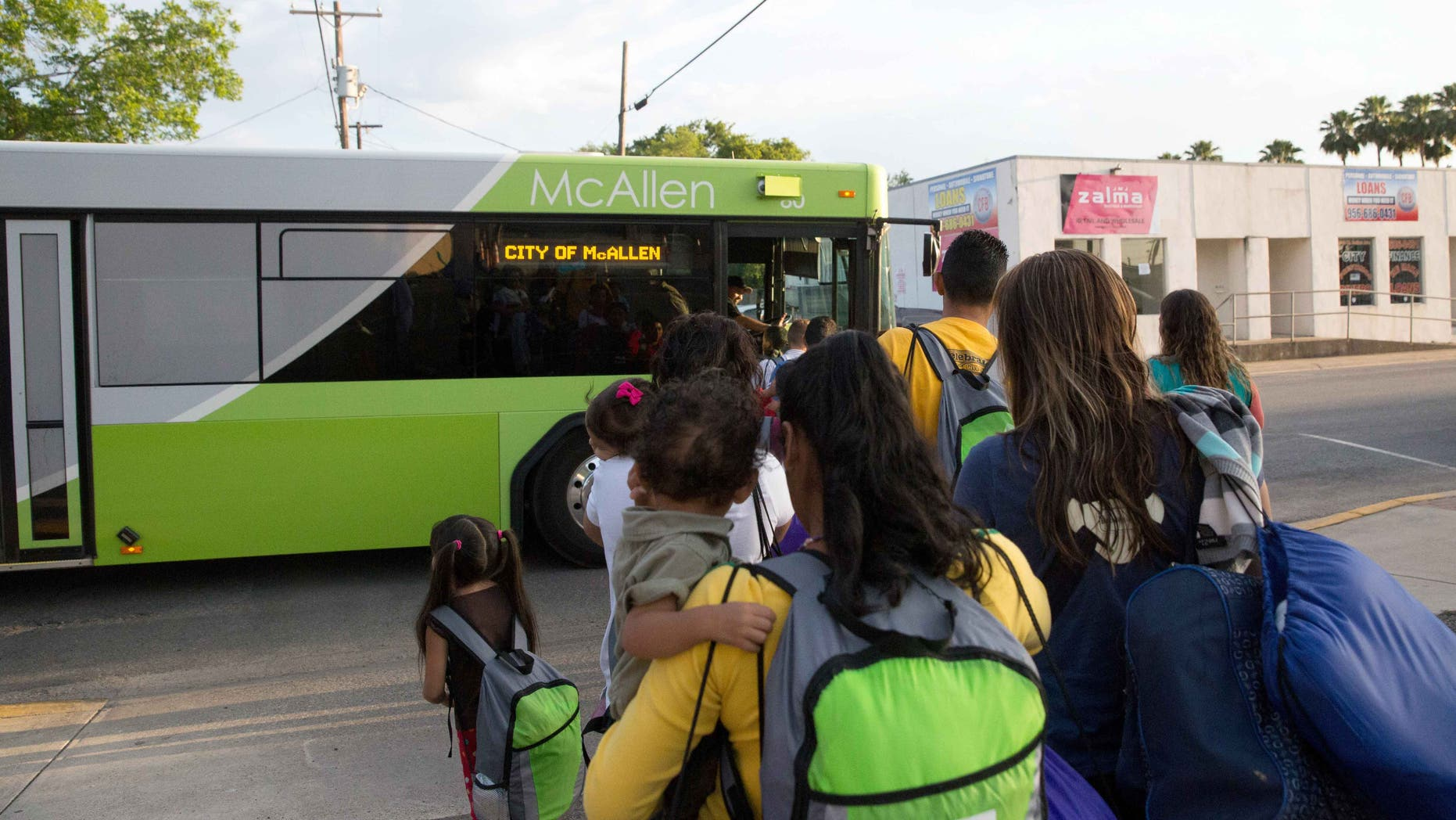 Immigrant families board a bus headed to the downtown bus station in McAllen, Texas on April 30, 2015.