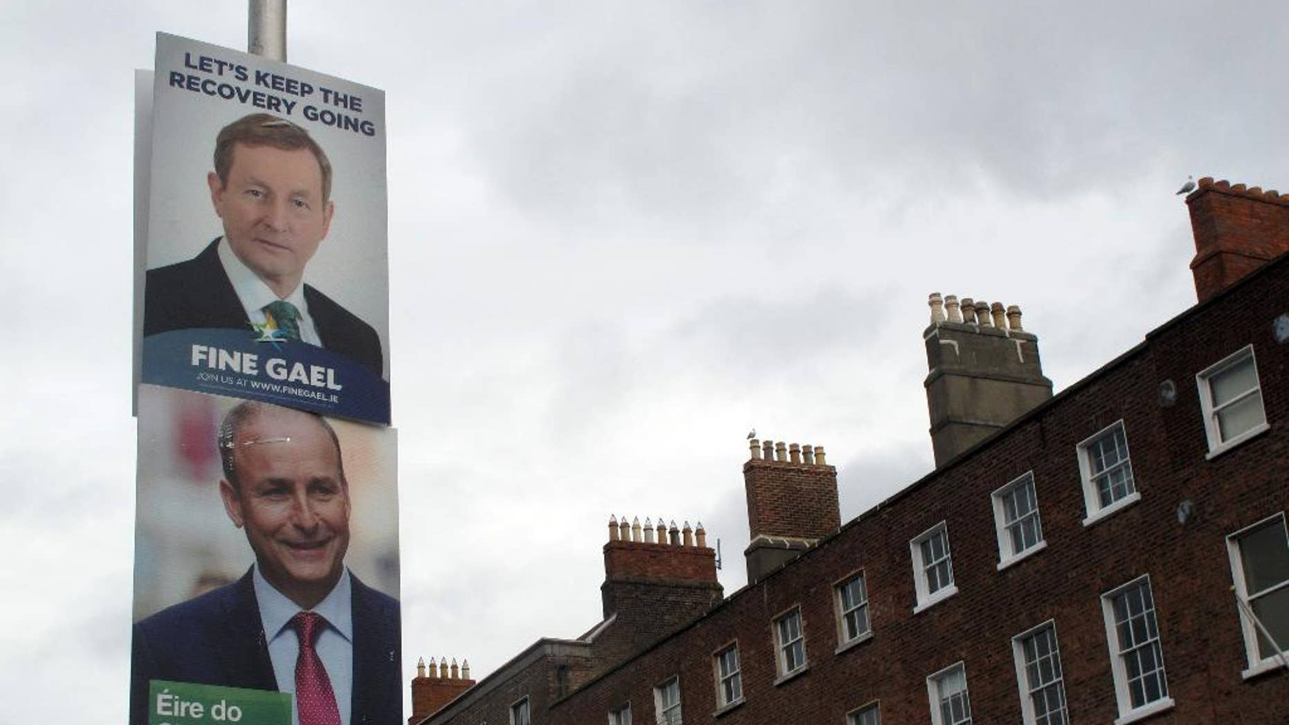 FILE - This  is a  Feb. 5, 2016 file photo, of  rival election posters for Fine Gael leader Enda Kenny and Fianna Fail leader Micheal Martin as they adorn a lamp post in Dublin, Ireland. Ireland's lawmakers have failed for a third time to elect a prime minister. Thursday's, April 14, 2016, stalemate leaves the country in political limbo for a record 48 days following an inconclusive Feb. 26 election.(AP Photo/Shawn Pogatchnik, File)