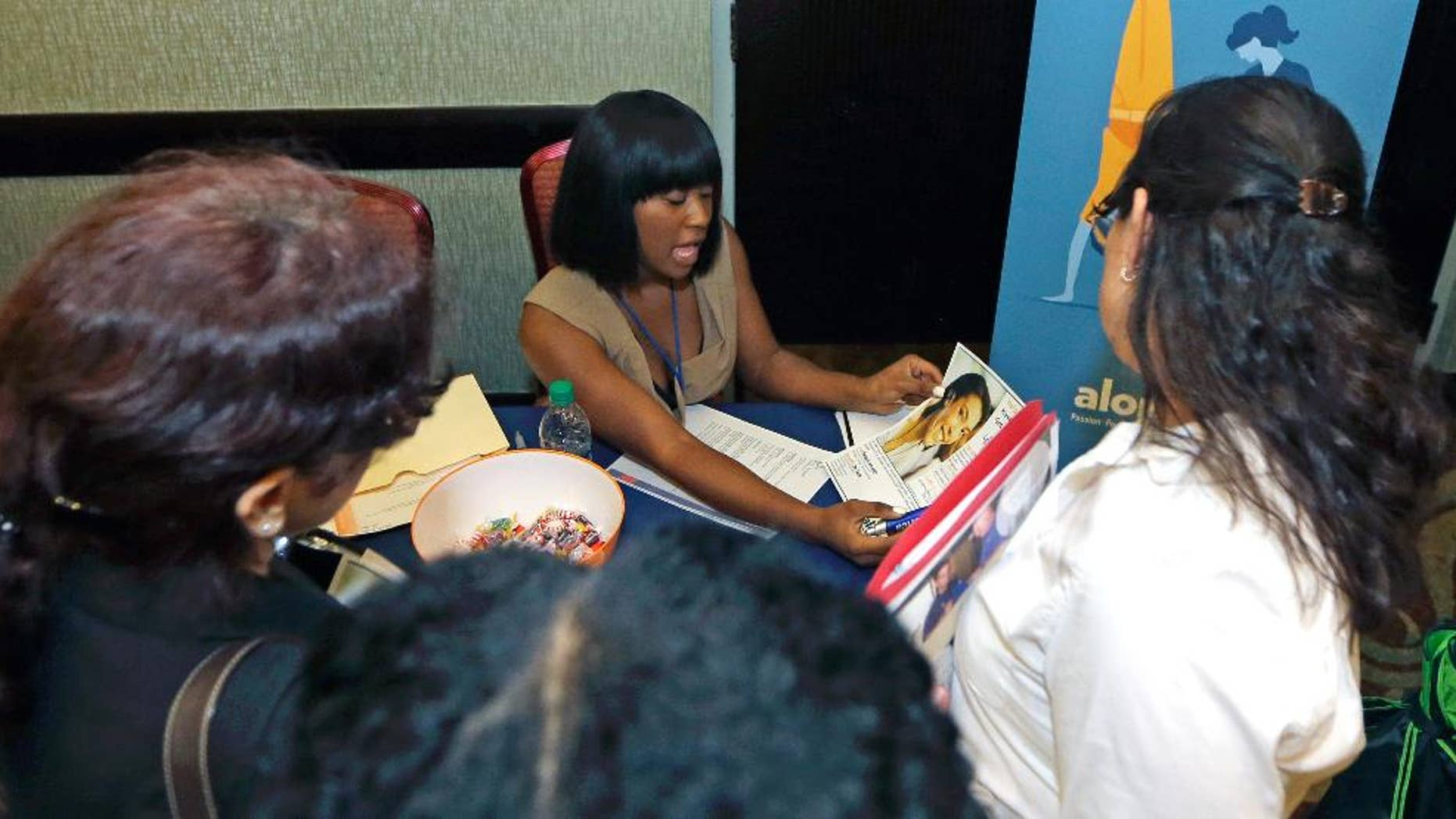 In this photo taken Wednesday, July 15, 2015, Janell Maycock gives information about job opportunities to job seekers at a job fair in Miami Lakes, Fla.  Payroll processor ADP reports how many jobs private employers added in August on Wednesday, Sept. 2, 2015. (AP Photo/Alan Diaz)