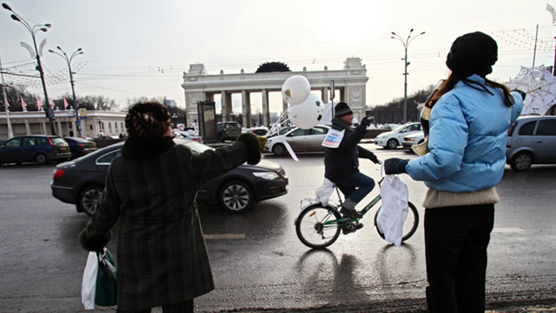 Feb. 19: People standing on a sidewalk wave in support to the participants of the motorist's rally in Moscow.