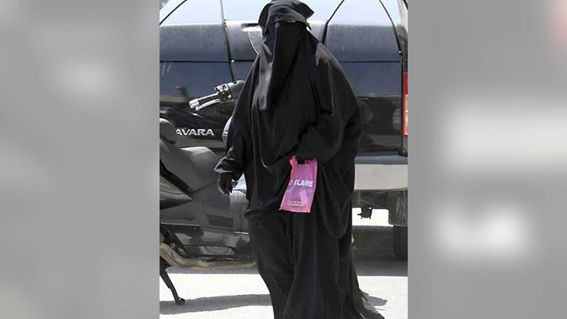 File: An unidentified woman wears Muslim style dress, with only her eyes visible, in Marseille, southern France.