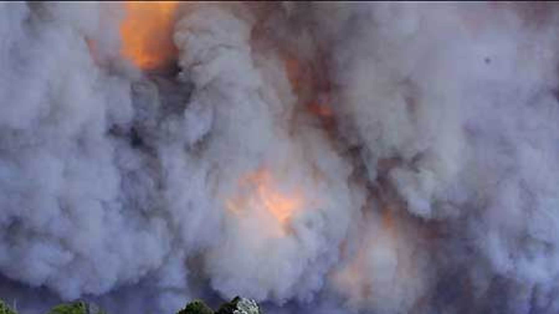 Feb. 7: An emergency vehicle races away from a blaze near a structure in the Gippsland region in Australia's Victoria state.
