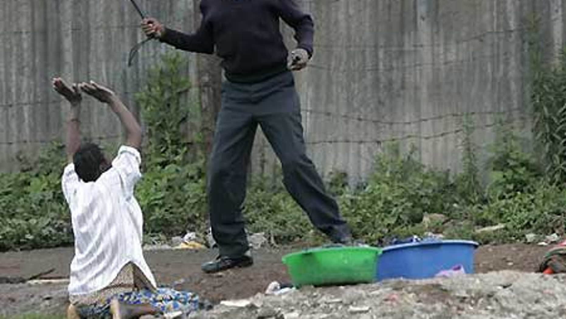 File: A woman who was washing her laundry when police fired tear gas begs a policeman not to beat her in Nairobi slum.