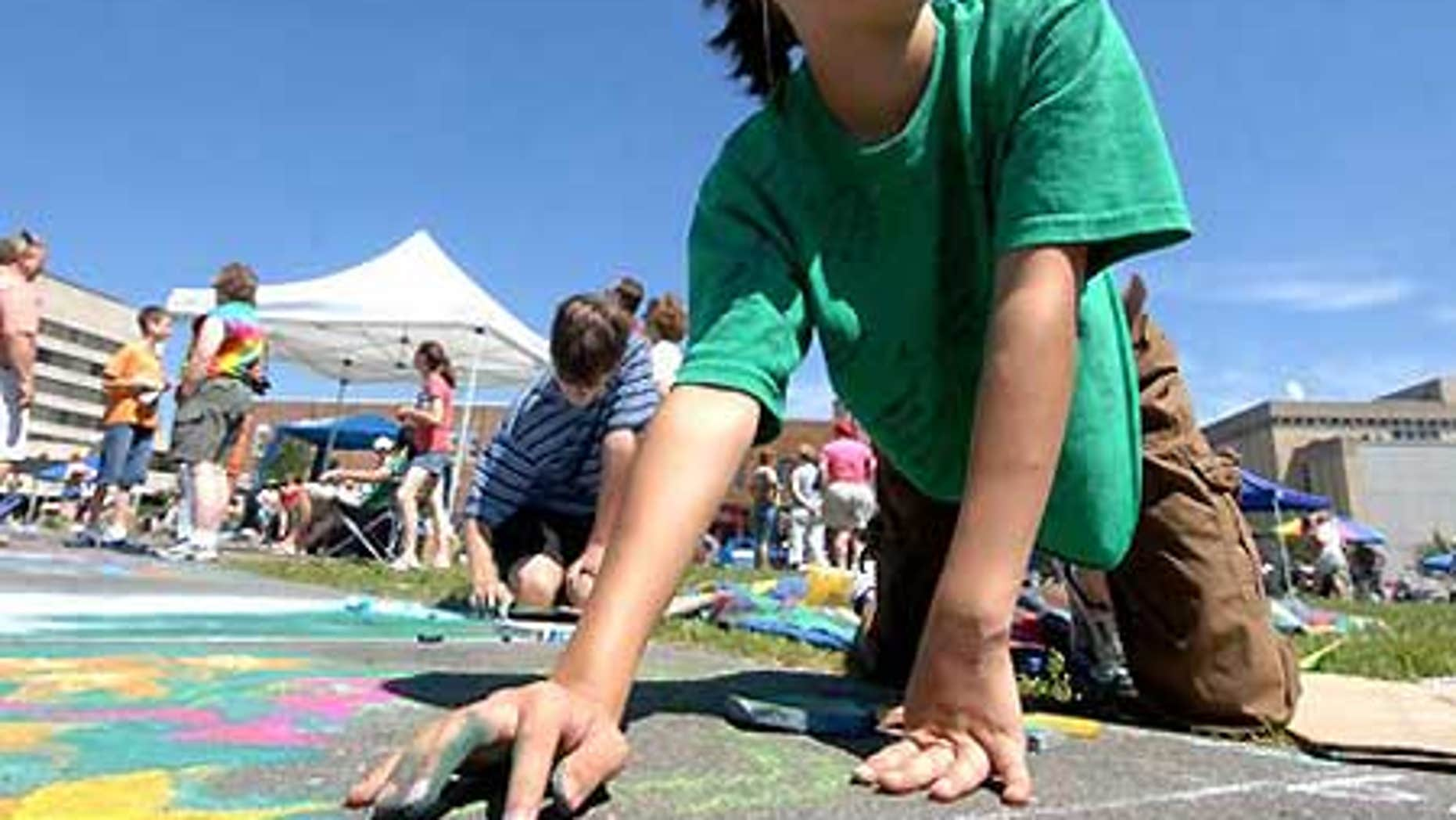 Madeline Kara Neumann works on chalk art during downtown Wausau's annual Chalk Fest.