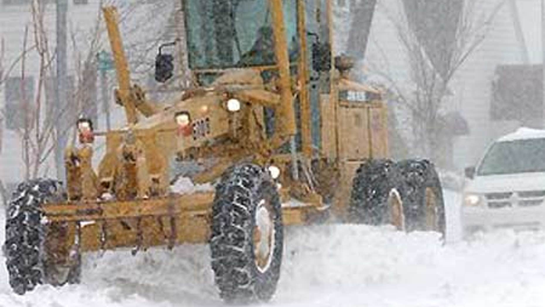 Garden City, Kansas, city employee Jim Brungardt drives a road grader to push fallen snow as snow continues to accumulate.