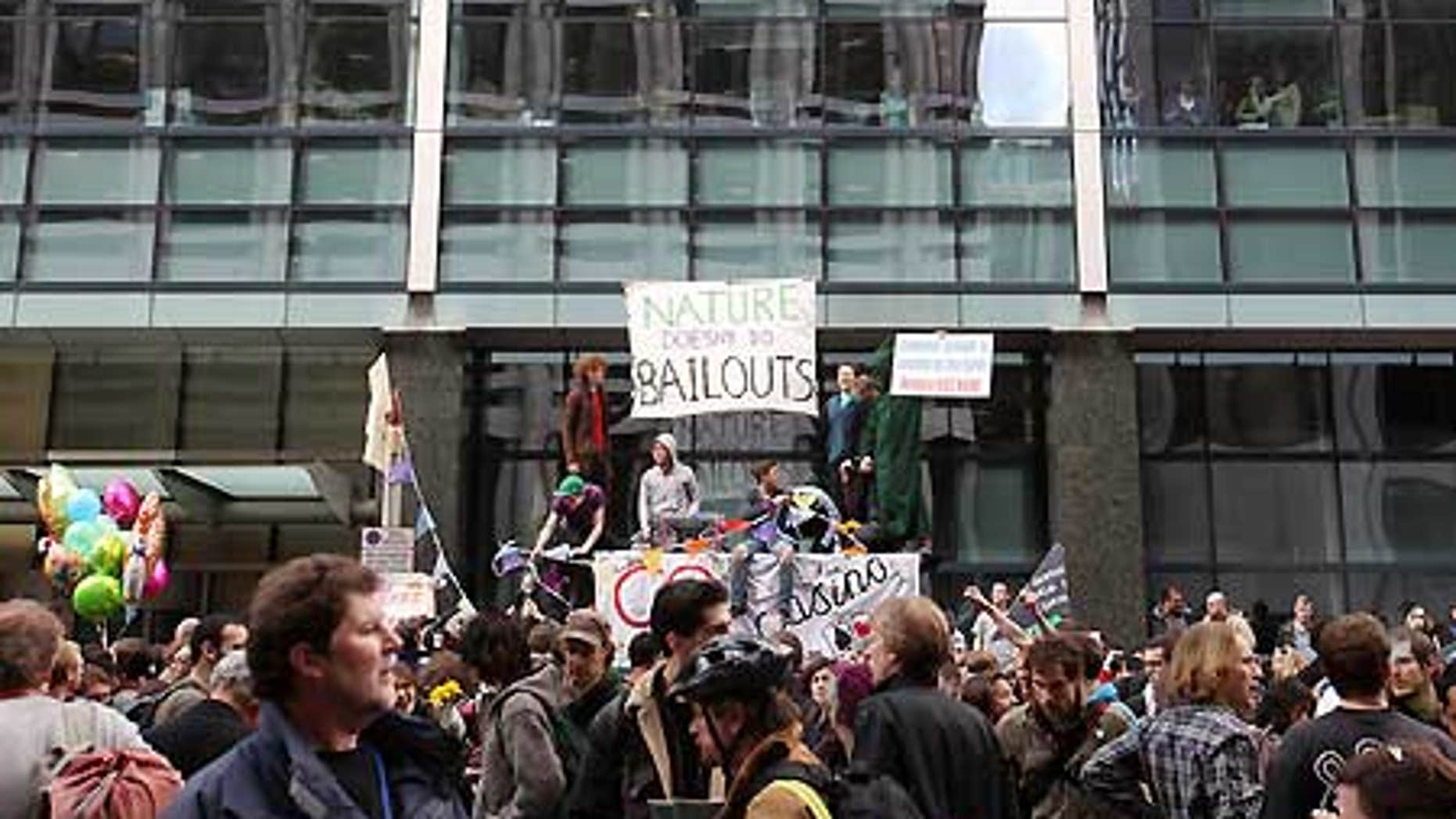 April 1: Protesters sit atop a bus stop in London's financial district as office workers watch from windows.