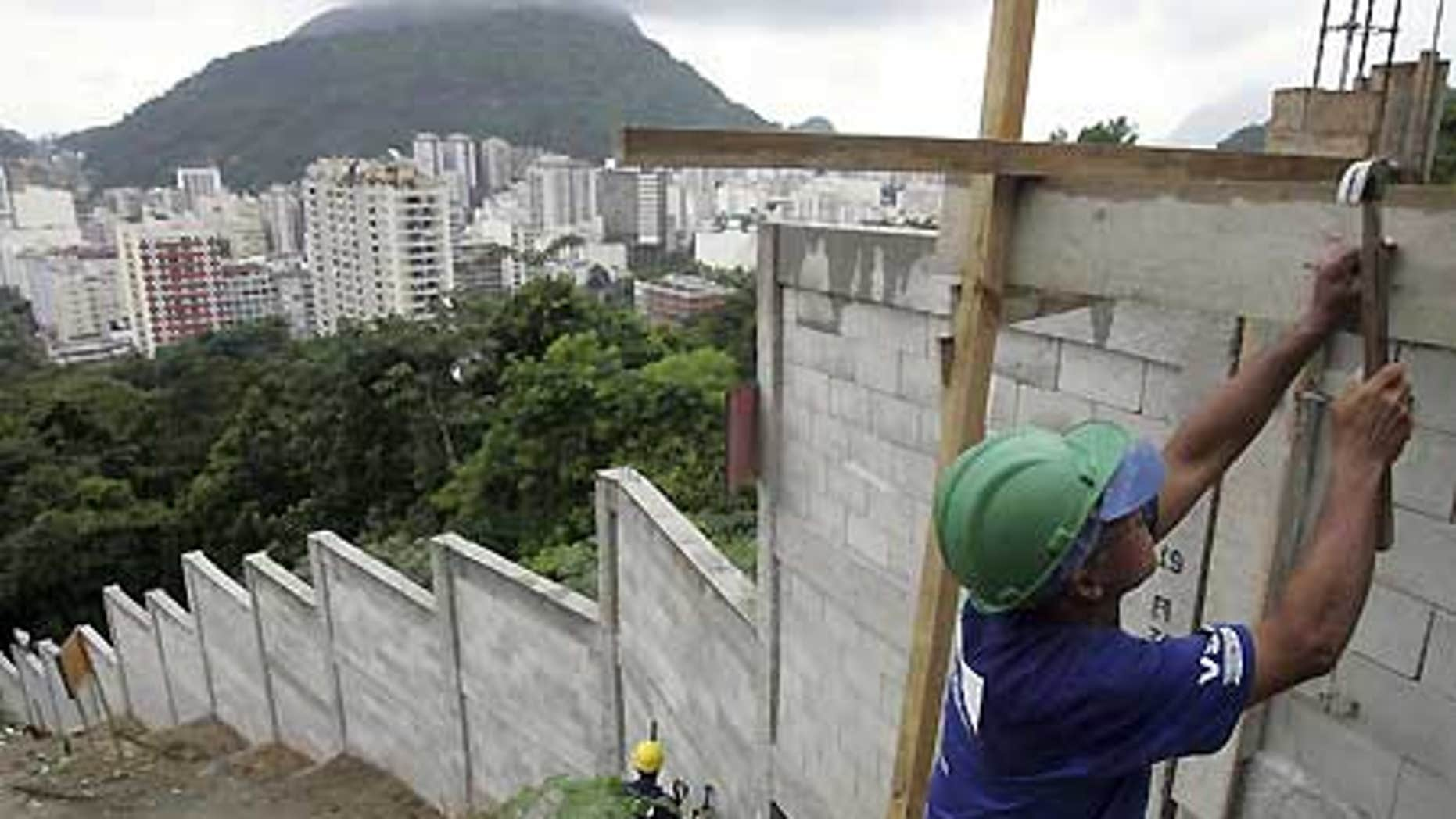 March 31: A worker builds a wall at the Dona Marta slum in Rio de Janeiro.