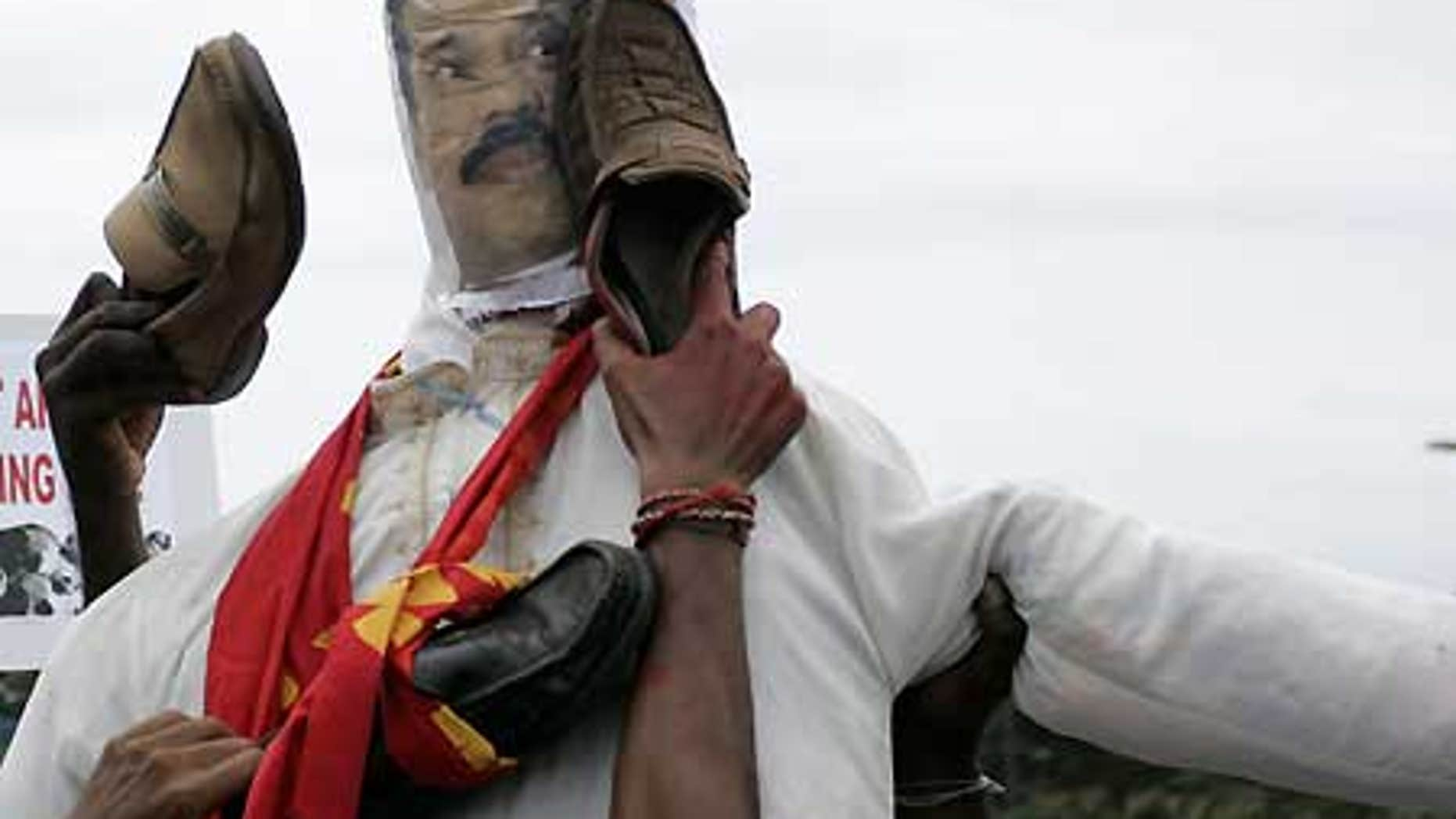 April 21: Malaysian Indian protesters of Tamil ethnicity beat an effigy of Sri Lankan President Mahinda Rajapaksa with shoes.