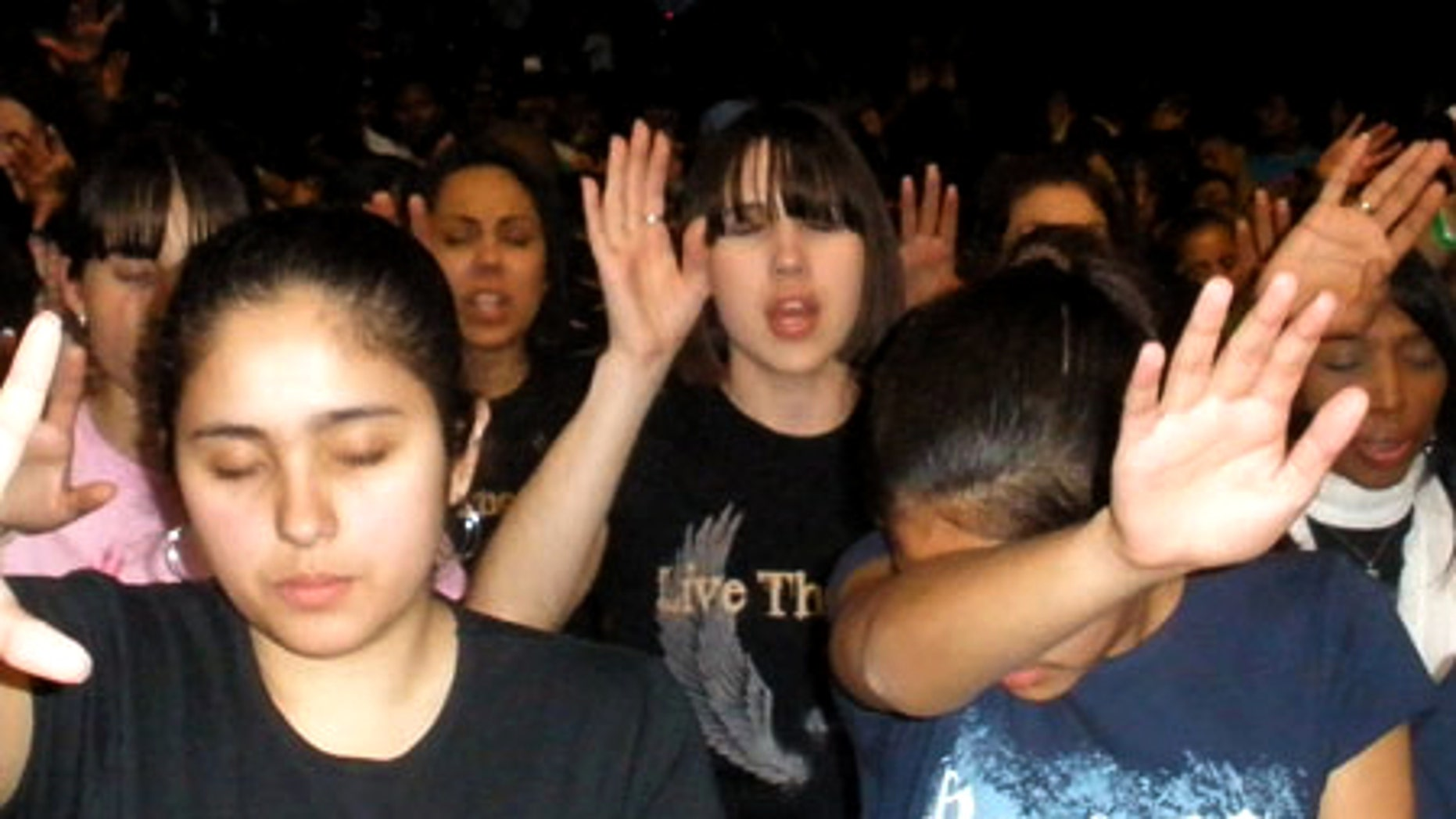 April 18: Concertgoers reach their hands up in prayer during a moment of worship at at the IZOD Center in New Jersey.
