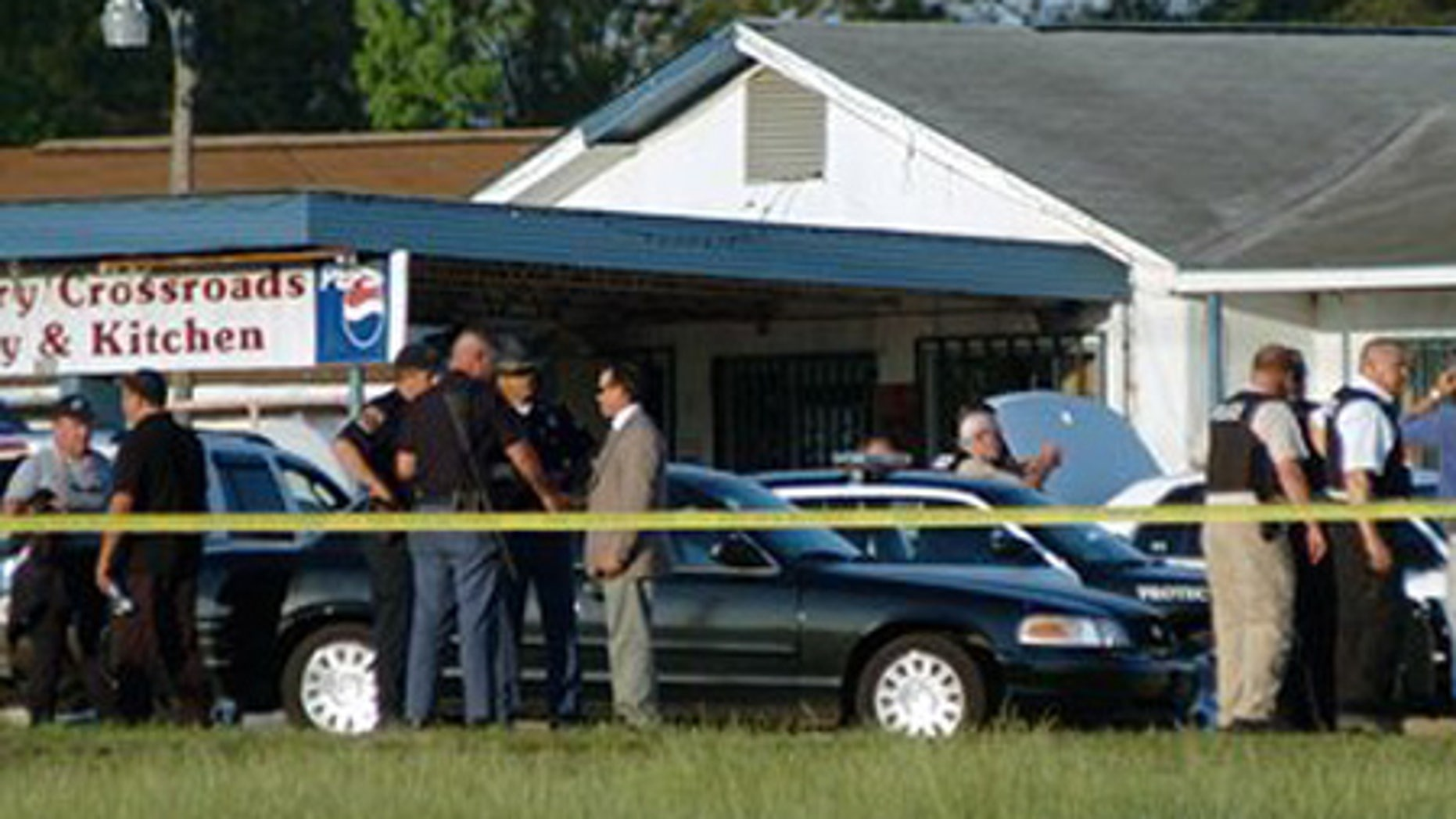 April 24: Law enforcement personnel and first responders work the scene of a shooting that left one police officer and the suspect dead in Alabama.