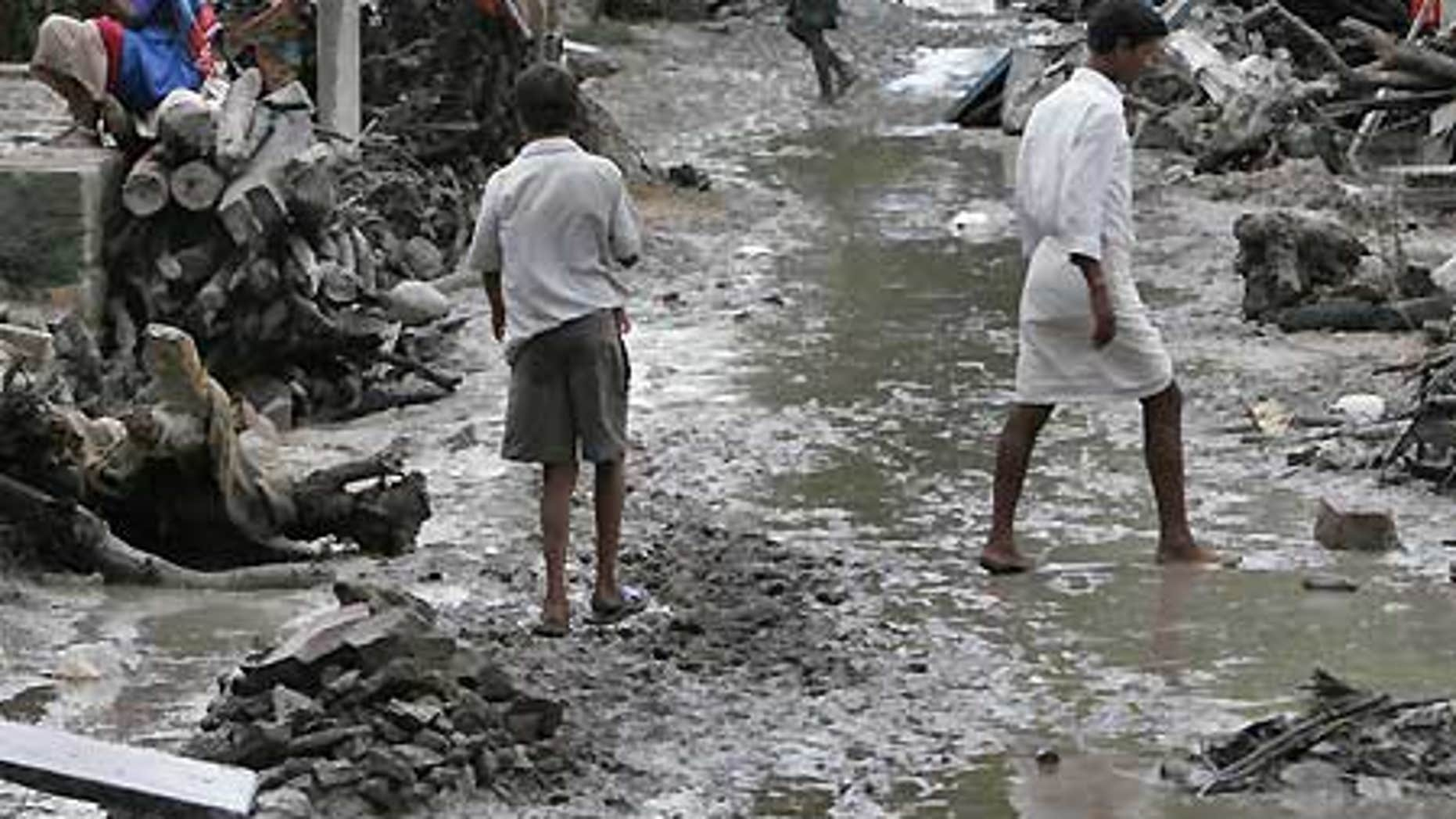 Oct. 3: Villagers walk through a neighborhood badly damaged by floodwaters in Kudadarahal village.