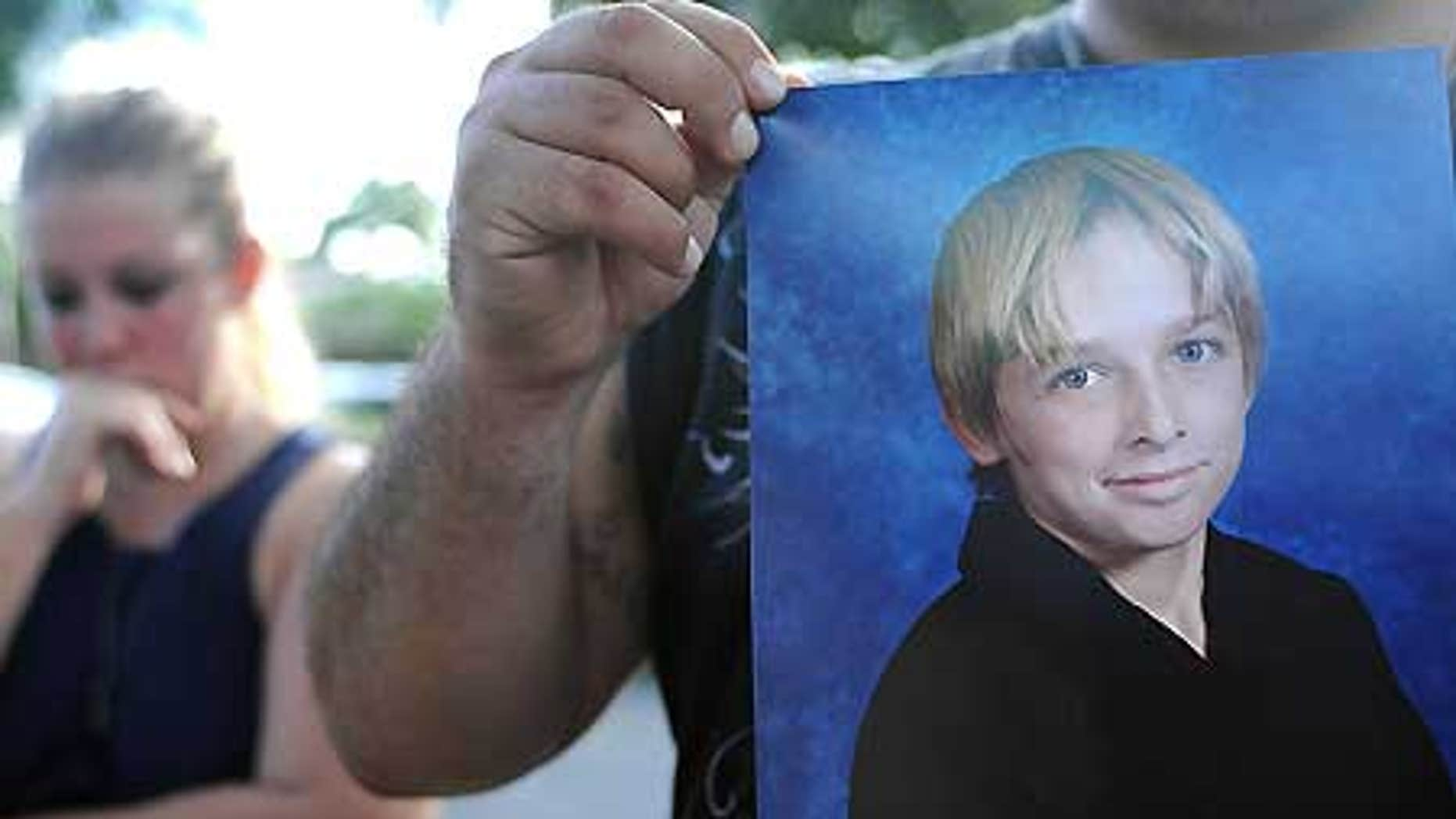 Oct. 13: Danny Martinez, unseen, holds a photo of his brother-in-law, Michael Brewer, 15, who was set on fire.
