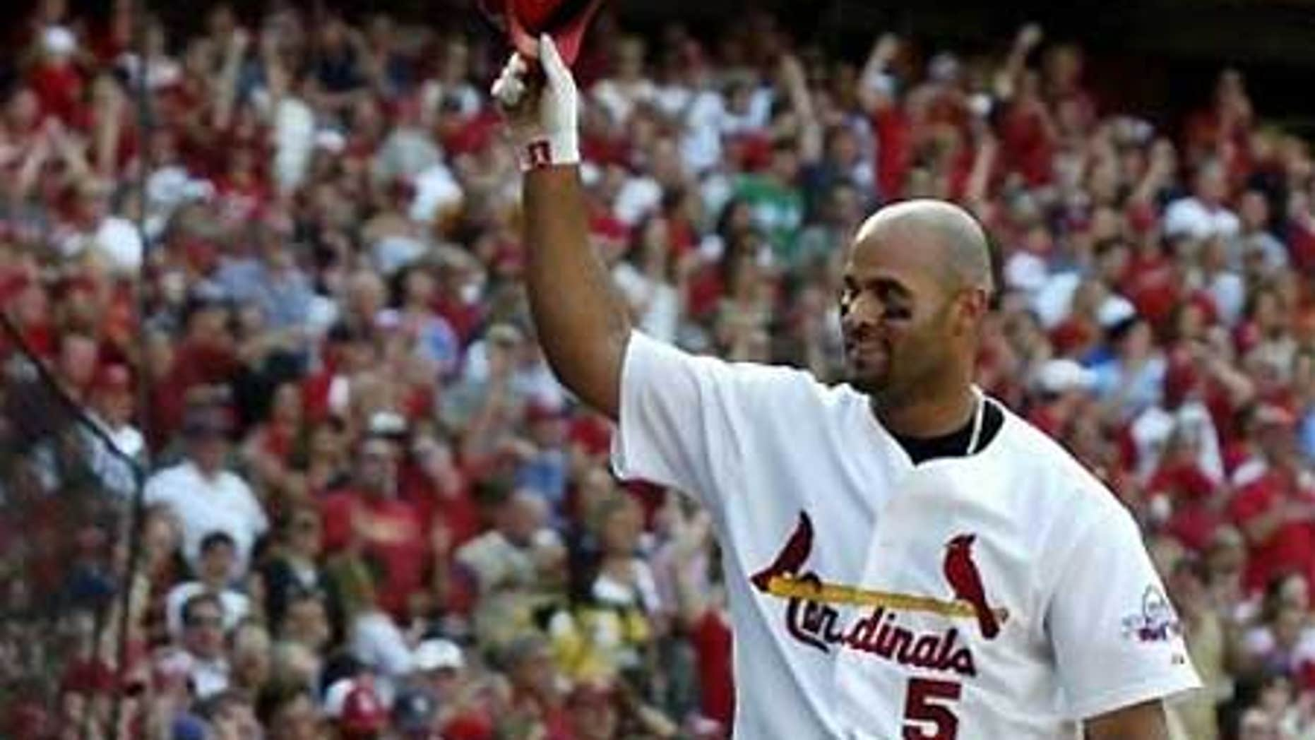 April 25: Albert Pujols tips his helmet to the crowd after hitting a seventh-inning grand slam against the Cubs.