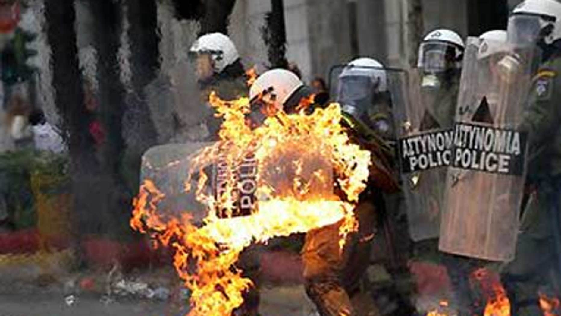 Dec. 6: A riot policeman's clothing catches fire after demonstrators threw petrol bombs at them, as violence erupted.