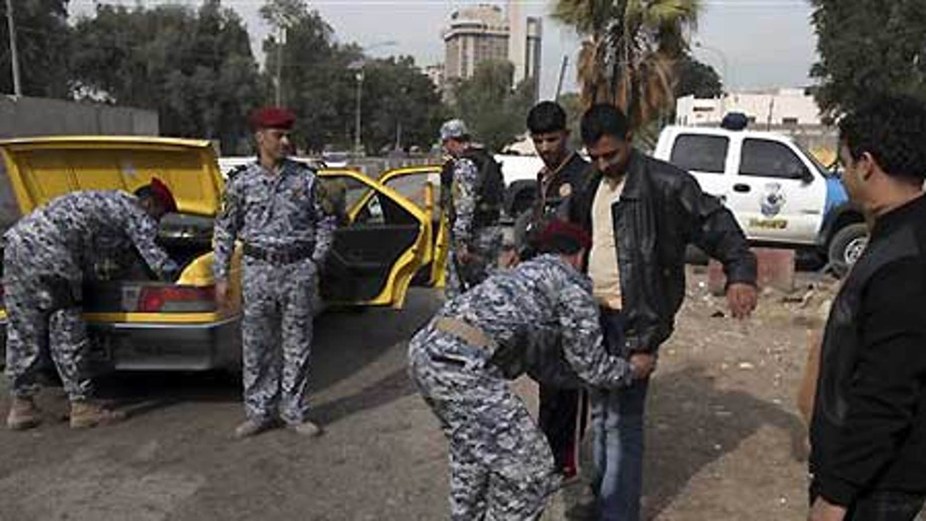 Dec. 14: Iraqi policemen search a man and his car at checkpoint in central Baghdad, Iraq.
