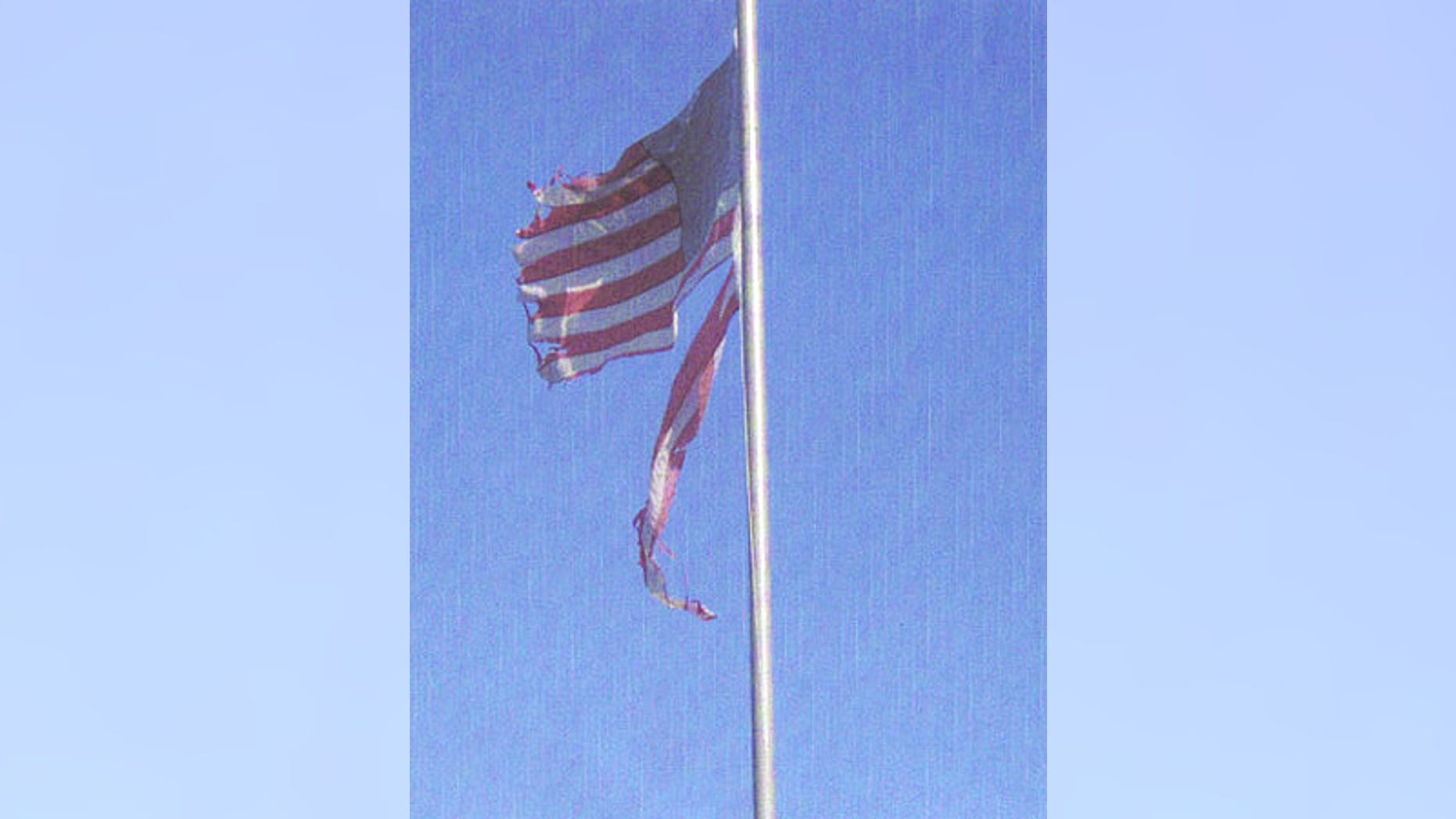 Despite calls by neighbors, this weathered U.S. flag won't come down until Corporal Paul Haros, U.S. Army Reserves, returns to California.