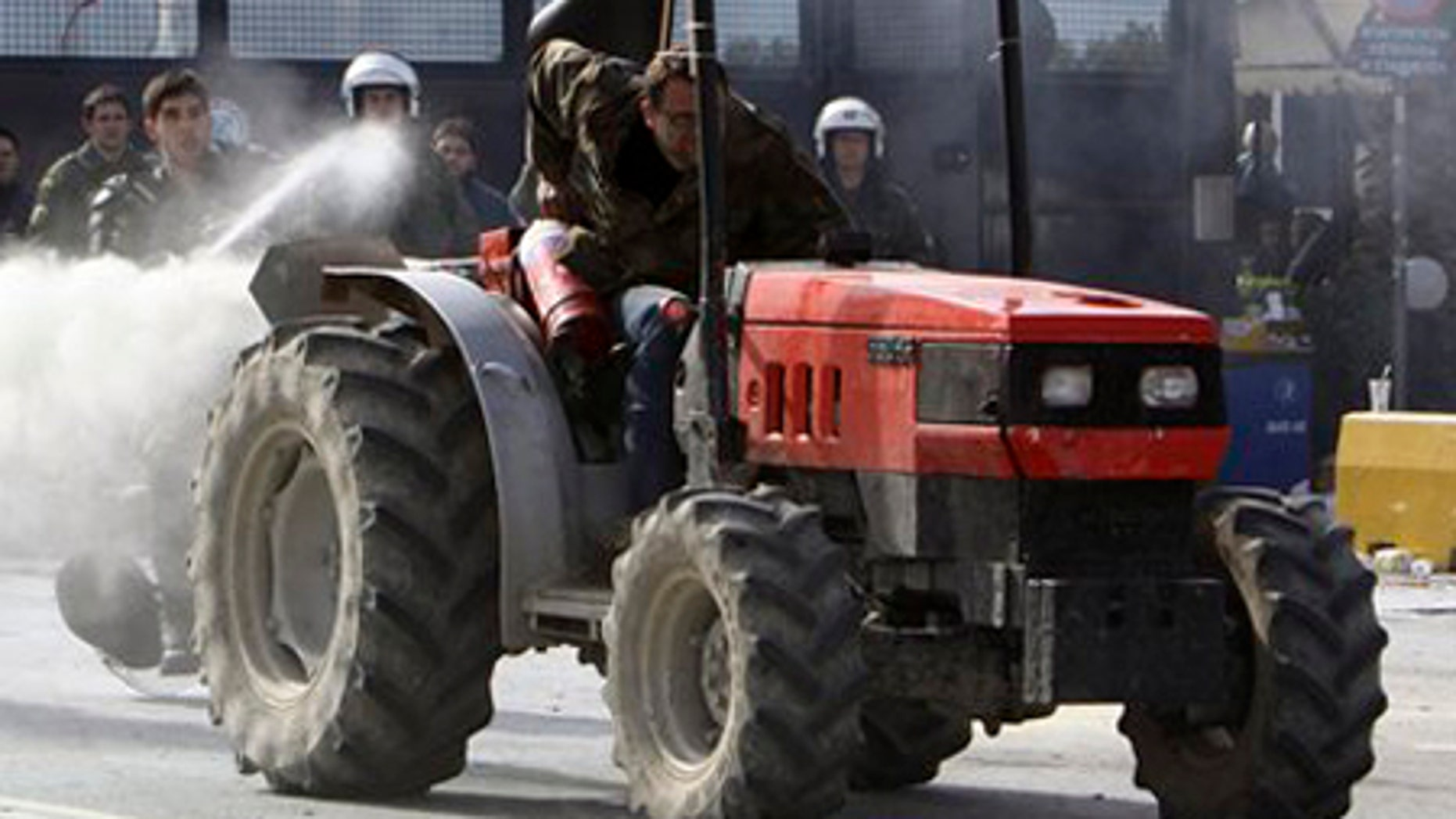 Feb. 3: A farmer riding a tractor uses a fire extinguisher against riot police, as a police officer responds with pepper spray, near Athens, Tuesday.