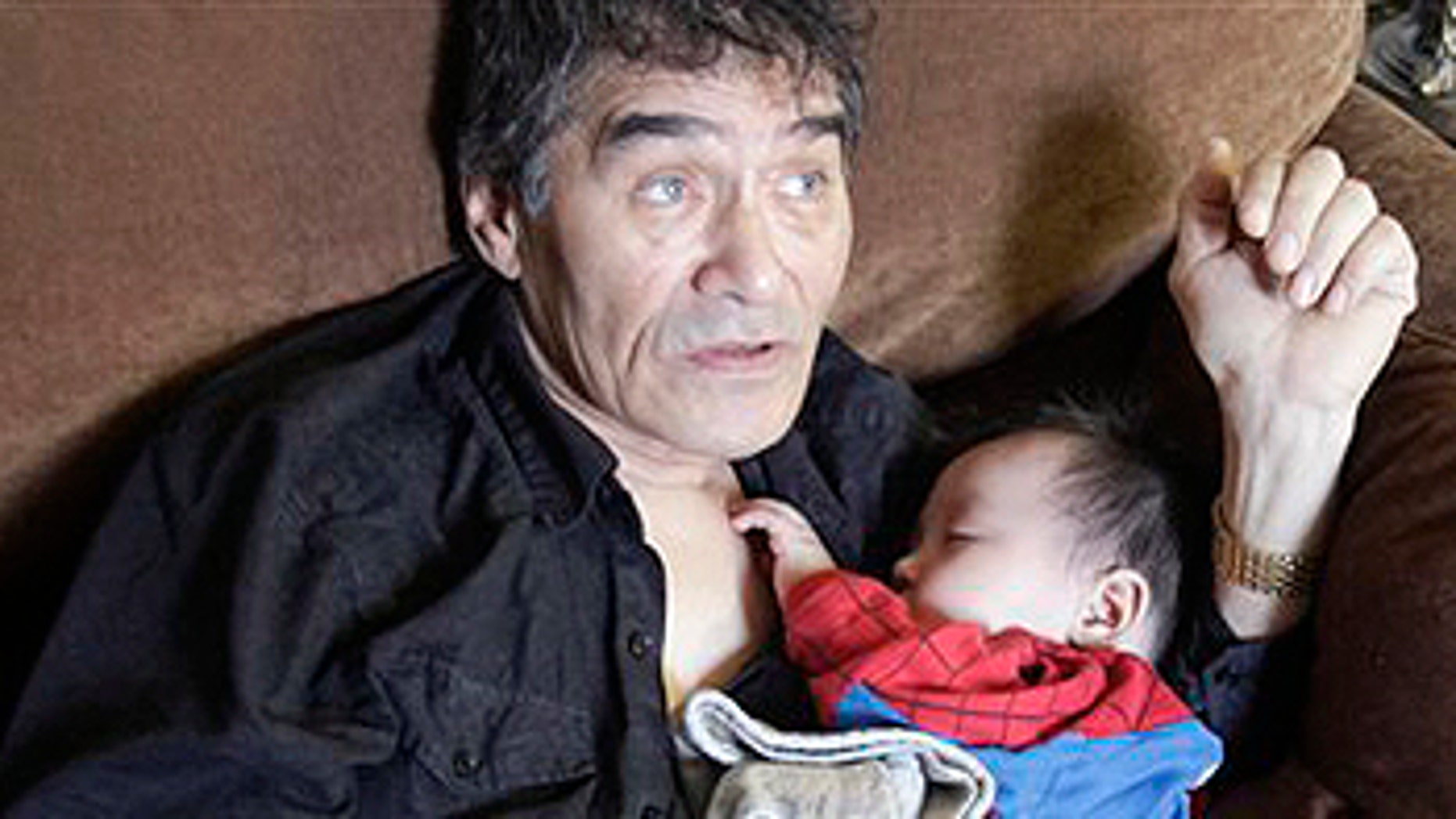 """In this Aug. 8, 2009 photo, Henry Nasogaluak Jr. sleeps in the arms of his father Henry Nasogaluak in Tuktoyaktuk, in the Northwest Territories, Canada. Henry Jr. slept in his father's arms as the hunter pondered the future of the boy born last Arctic winter, in the depths of a polar bear season he'd rather forget. """"It's too late to be a hunter. I don't want him to do that,"""" Henry Nasogaluak said of his son. """"It's a hard life, and it got harder with the ban by the United States."""" (AP Photo/Rick Bowmer)"""