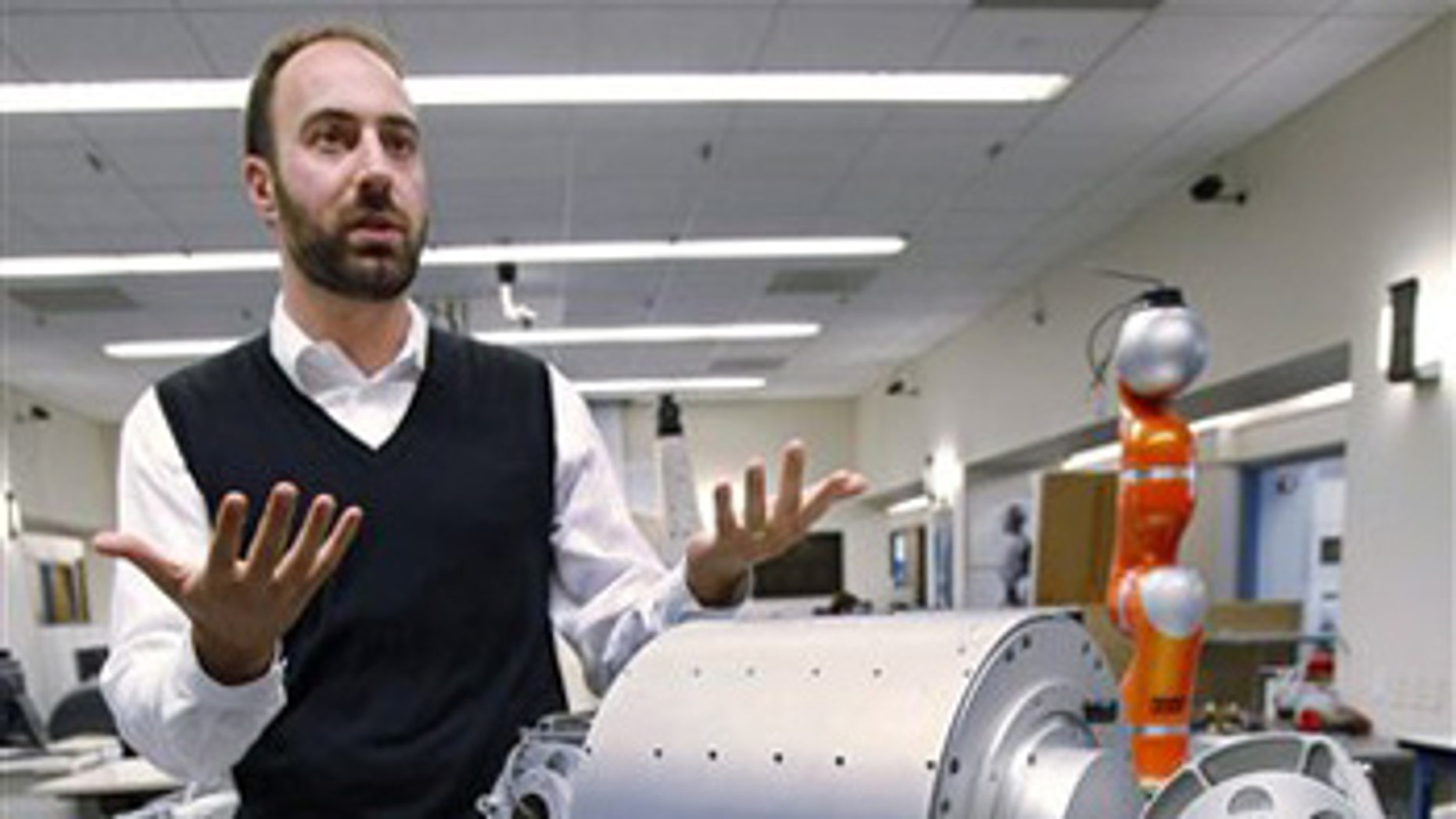Nov. 24: Ryan Calo stands next to a robot that is being built for medical applications at Stanford University's Artificial Intelligence Laboratory.