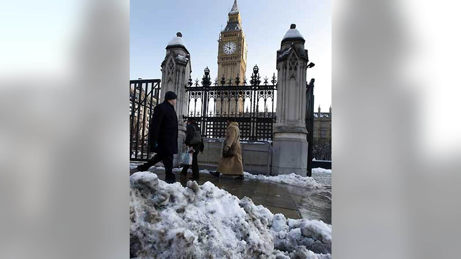 Feb. 3: Melting snow is seen as workers pass Big Ben in Westminster in London.