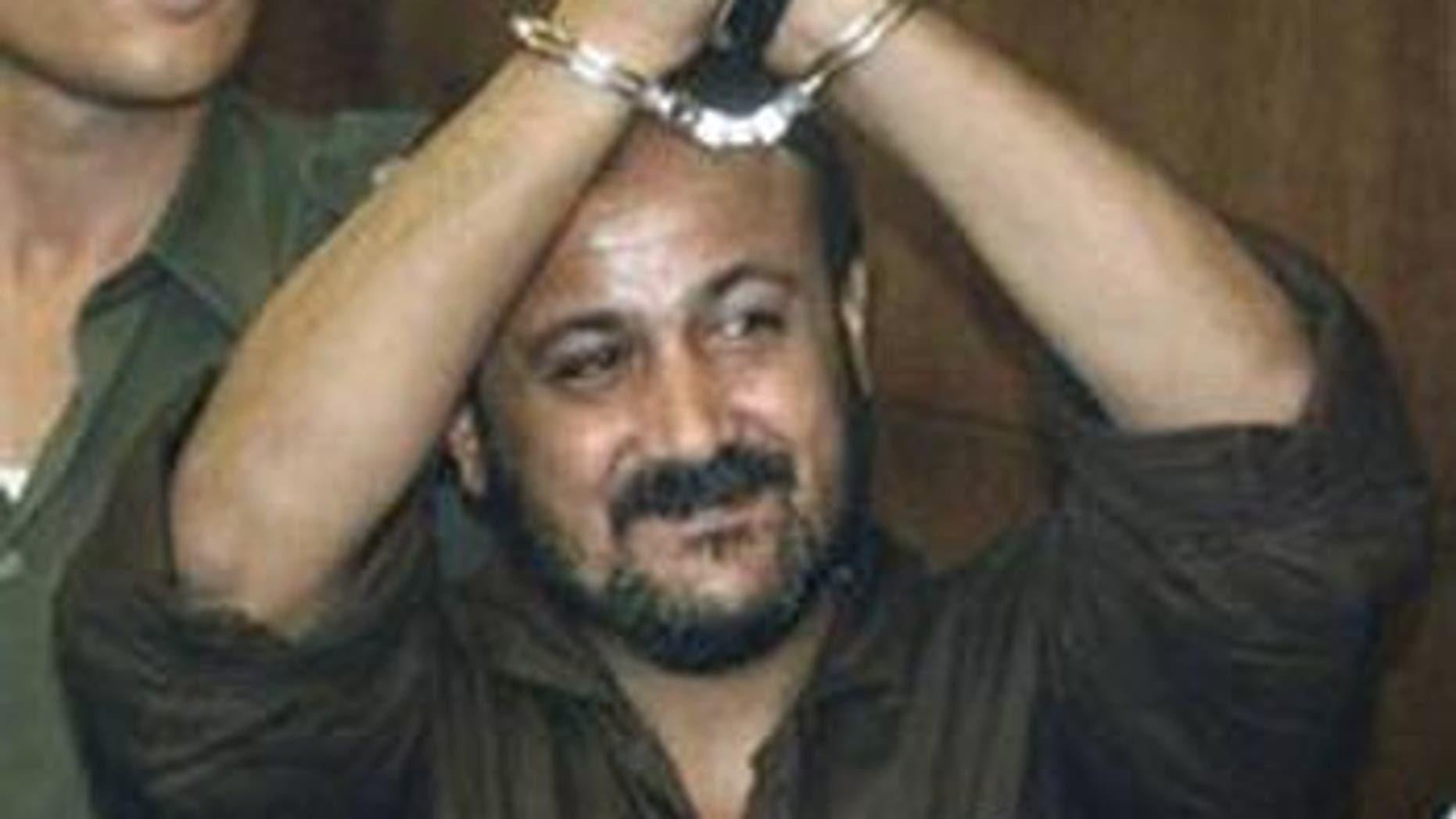 In this Aug. 14, 2002 file photo Marwan Barghouti raises his handcuffed hands in the air on the opening day of his trial at Tel Aviv's District Court