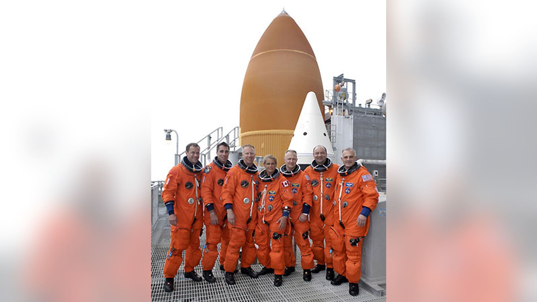 The STS-127 pose next to the top of Endeavour's orange fuel tank and twin solid-fuel rocket boosters.