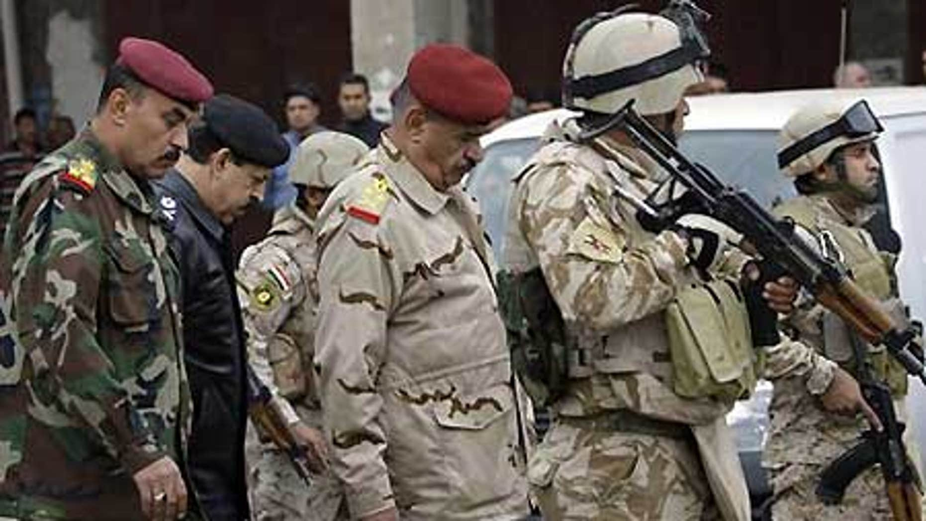 Dec. 8: Gen. Abboud Qanbar, center, escorted by bodyguards, inspects site of a bomb attack near the new Finance Ministry building in Baghdad, Iraq.