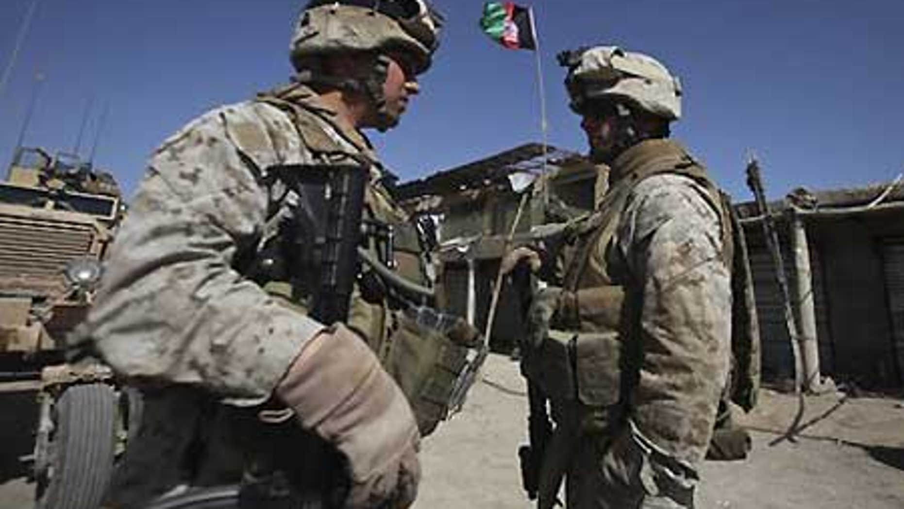 Feb. 17: U.S. Marines with NATO forces talk as newly raised Afghan flag is seen in the background at a deserted market of Marjah, Afghanistan.