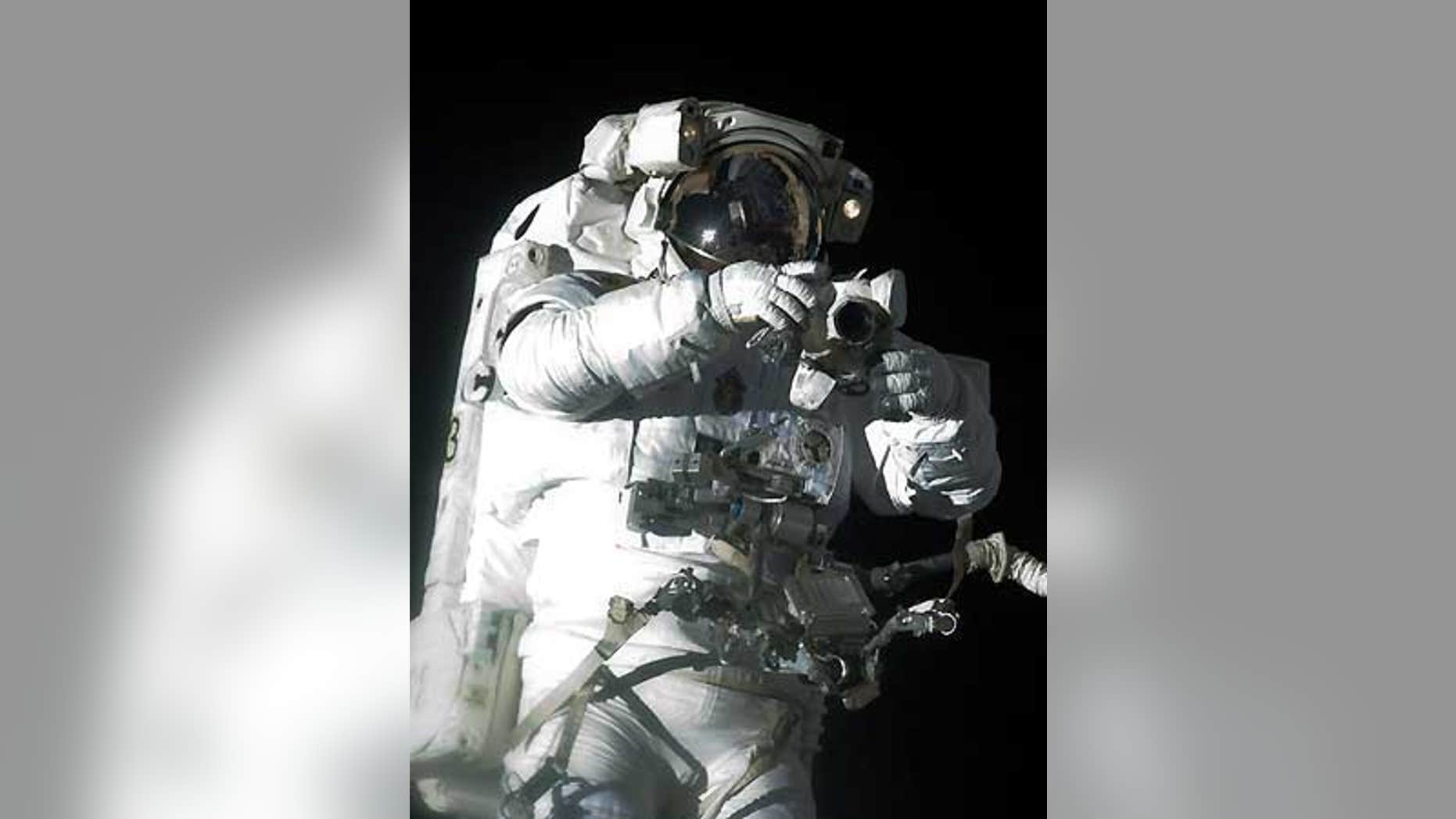 Atlantis shuttle astronaut Robert Satcher Jr. holds a camera during his mission's first spacewalk