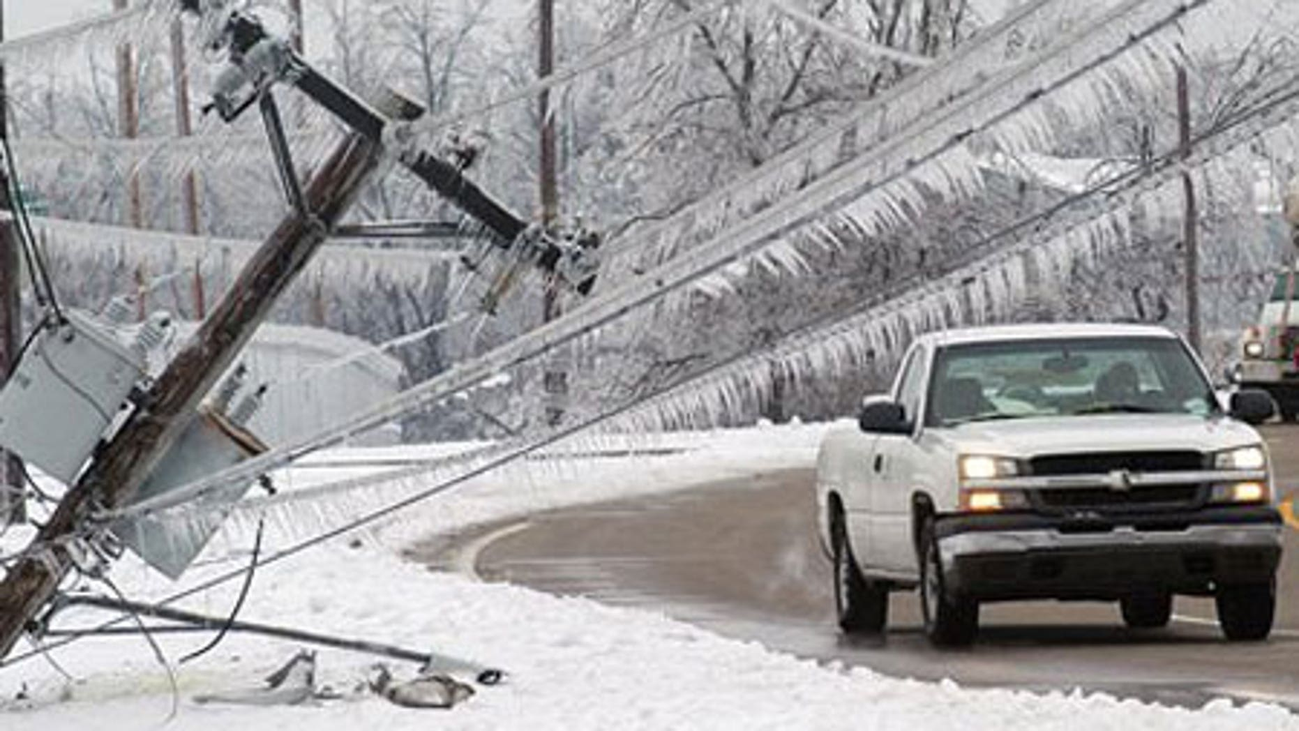 Jan. 31: A vehicle prepares to pass the top of a power pole that fell onto the sidewalk along 3rd Street in Paducah, Ky.
