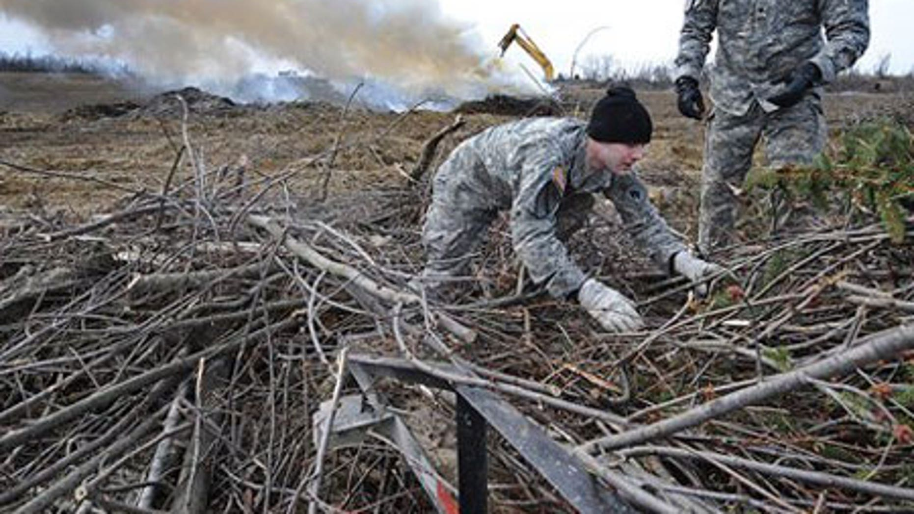 Feb. 2: Kentucky National guard members William Swartwood, left, and Jerry Bailey help unload branches from the back of a truck.
