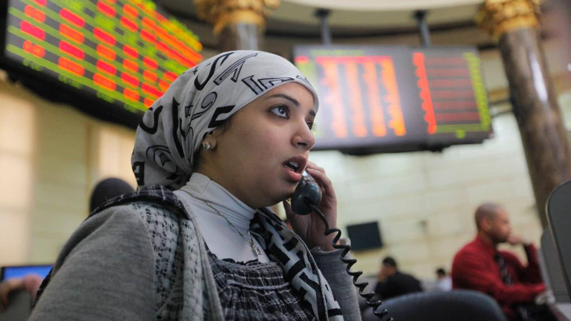 FILE - In this March 10, 2013 file photo, an Egyptian trader talks as she monitors her screen at the Egyptian Stock Exchange, in Cairo, Egypt.  Dubai-based Emaar Properties, the property developer behind the record-breaking Burj Khalifa skyscraper in Dubai, said Wednesday, May 20, 2015, that it will float shares in its Egyptian subsidiary on the Egyptian Stock Exchange to raise cash for ongoing and future projects in the North African nation. (AP Photo/Amr Nabil, File)