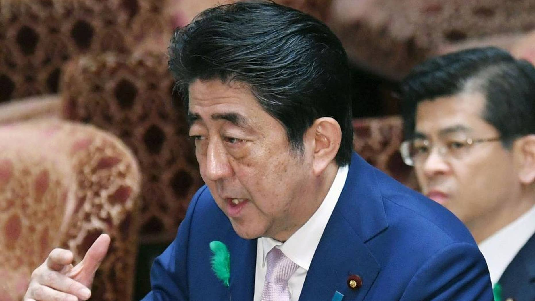 Japanese Prime Minister Shinzo Abe speaks during an Audit and Oversight of Administration Committee session at the lower house of Parliament in Tokyo Monday, April 17, 2017. Abe said Monday that Japan's government is drawing up contingency plans in case a crisis on the Korean Peninsula sends an influx of refugees to Japan. Abe told a parliamentary session that the government is formulating measures including protecting foreigners, landing procedures, building and operating shelters, and screening asylum seekers. (Yoshinobu Shimizu/Kyodo News via AP)