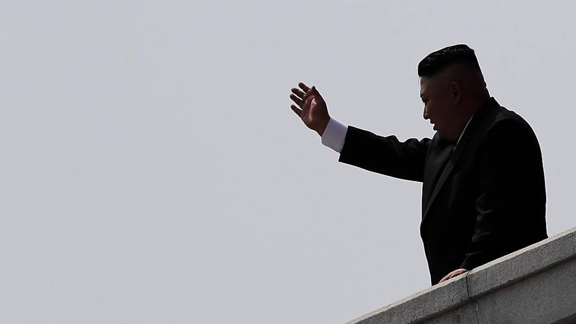 North Korean leader Kim Jong Un is seen in silhouette as he waves during a military parade on Saturday, April 15, 2017, in Pyongyang, North Korea to celebrate the 105th birth anniversary of Kim Il Sung, the country's late founder and grandfather of current ruler Kim Jong Un. (AP Photo/Wong Maye-E)