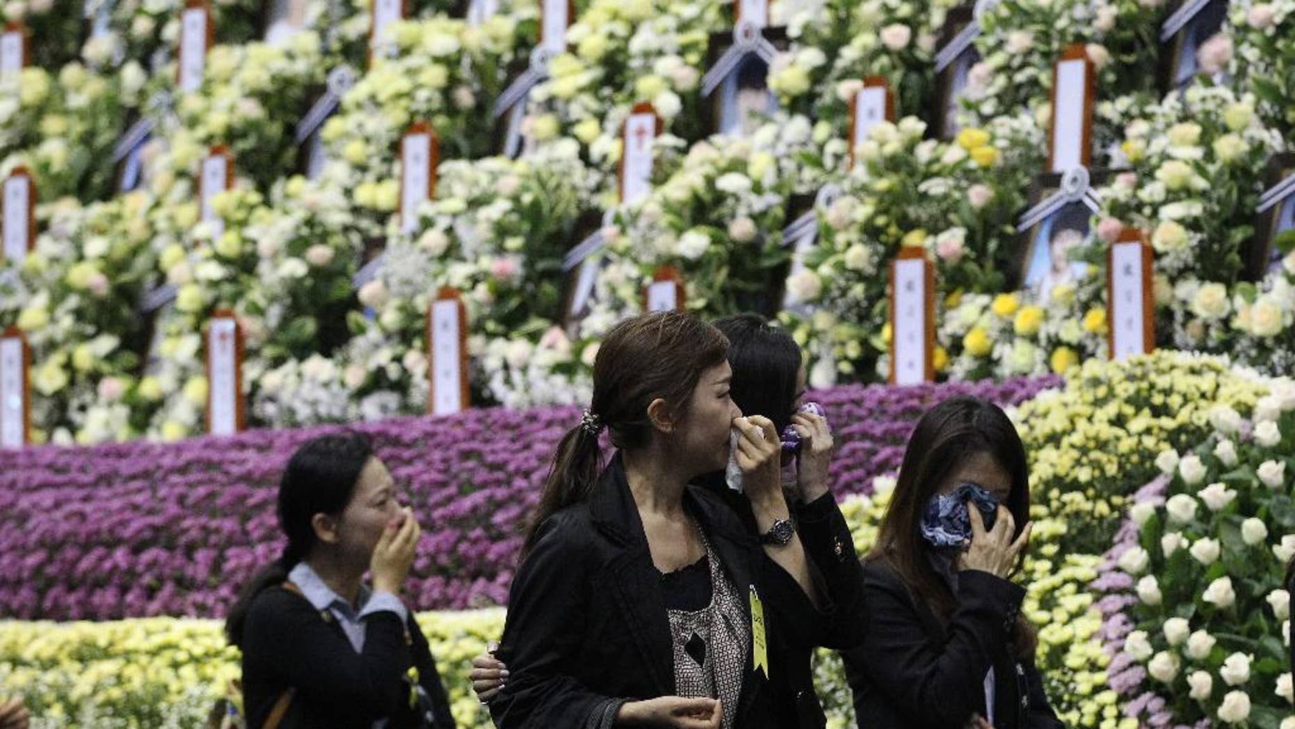 People weep as they pay tribute to the victims of the sunken ferry Sewol at a group memorial altar in Ansan, south of Seoul, South Korea, Tuesday, April 29, 2014. South Korean President Park Geun-hye apologized Tuesday for the government's inept initial response to a deadly ferry sinking as divers fought strong currents in their search for nearly 100 passengers still missing nearly two weeks after the accident.(AP Photo/Ahn Young-joon)