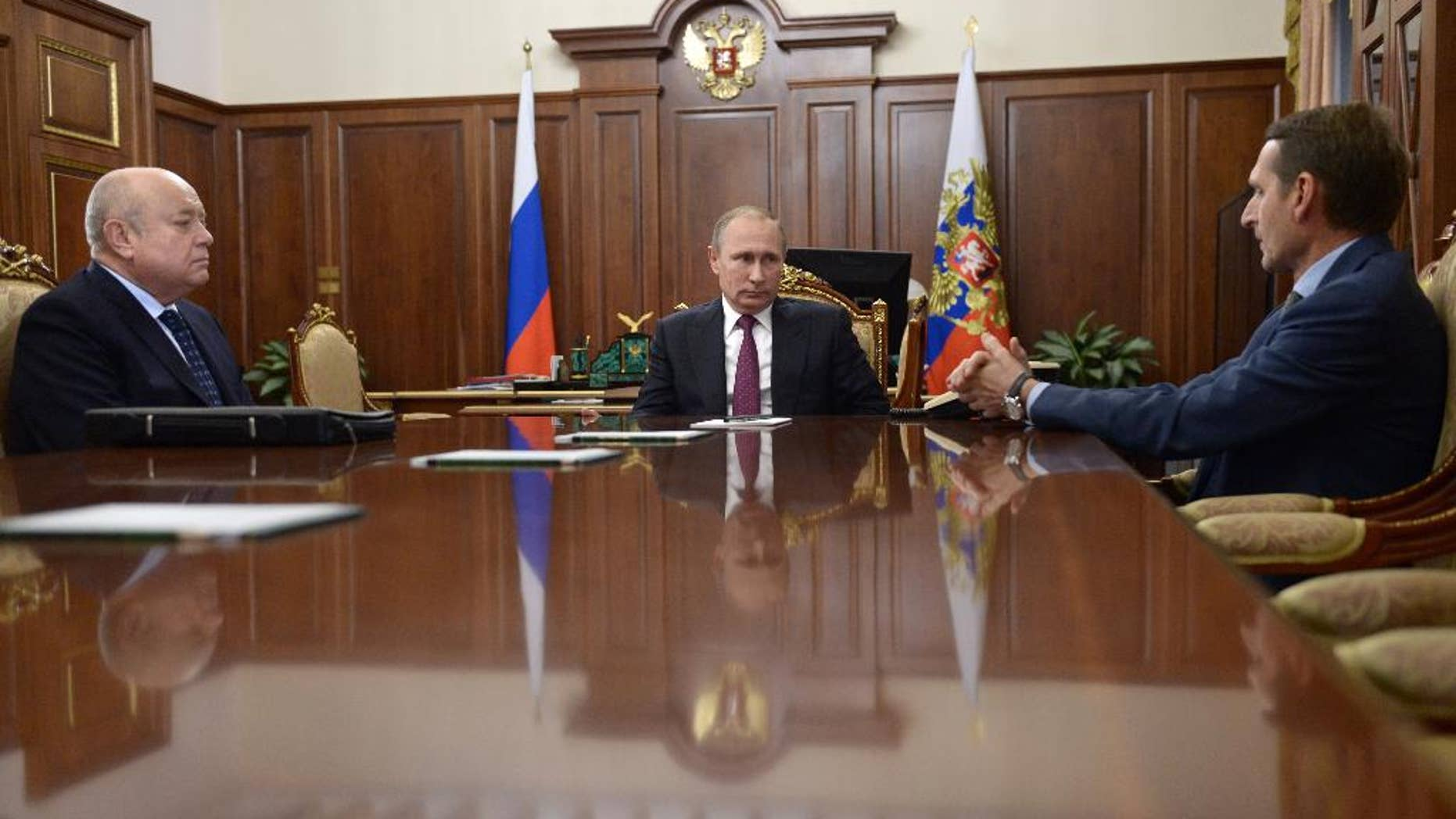 From left, Foreign Intelligence Service head Mikhail Fradkov, Russian President Vladimir Putin, and parliament speaker Sergei Naryshkin meet in Moscow's Kremlin Russia, Thursday, Sept. 22, 2016. Putin offered Fradkov a post of a head of board of directors of the Russian railways and Naryshkin a post of a head of Foreign Intelligence Service. (Alexei Nikolsky/Sputnik, Kremlin Pool Photo via AP)