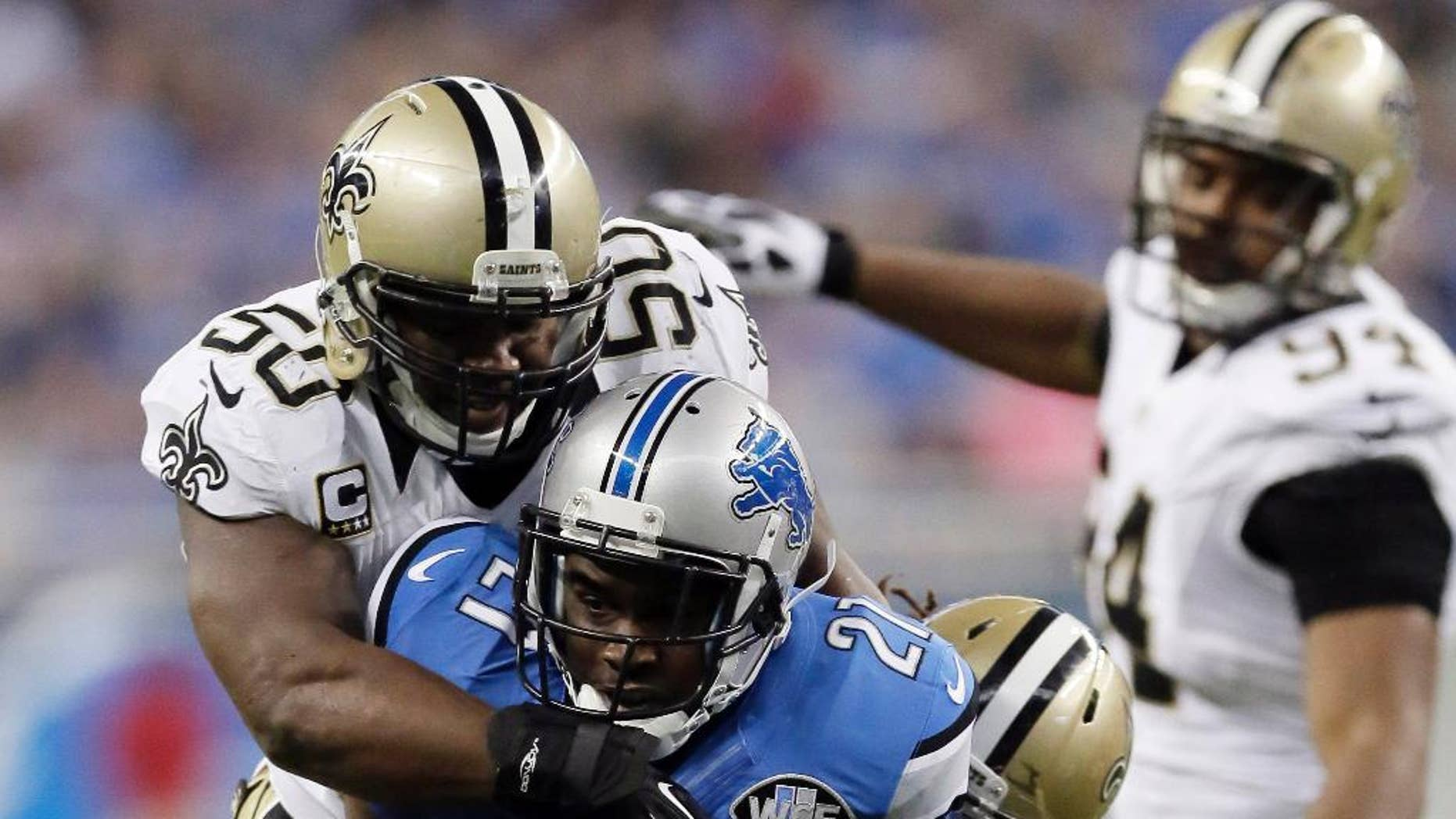 Detroit Lions running back Reggie Bush (21) is stopped by New Orleans Saints middle linebacker Curtis Lofton (50) and defensive back Marcus Ball (36) during the first half of an NFL football game in Detroit, Sunday, Oct. 19, 2014. (AP Photo/Duane Burleson) i