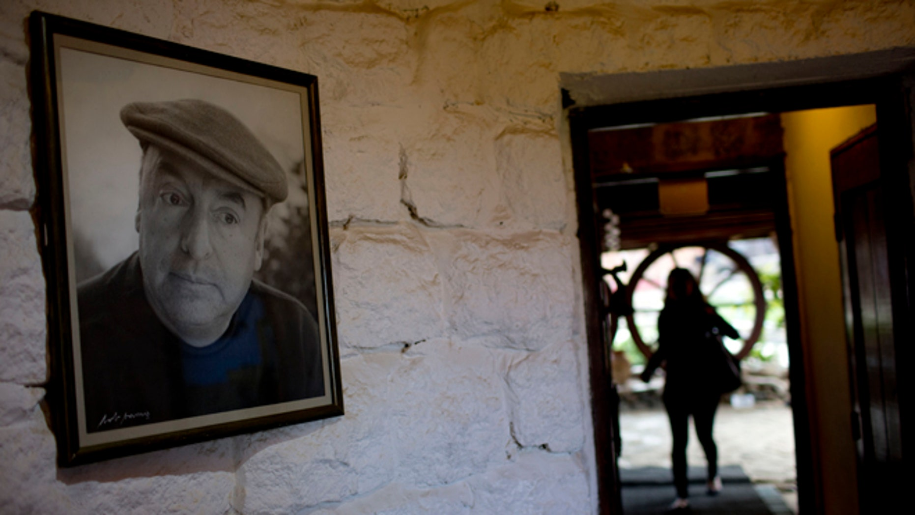 In this April 26, 2015 photo, a framed photo of Nobel Prize-winning poet Pablo Neruda hangs on a wall, as a tourist enters his favorite home in Isla Negra, Chile. (AP Photo/Natacha Pisarenko)